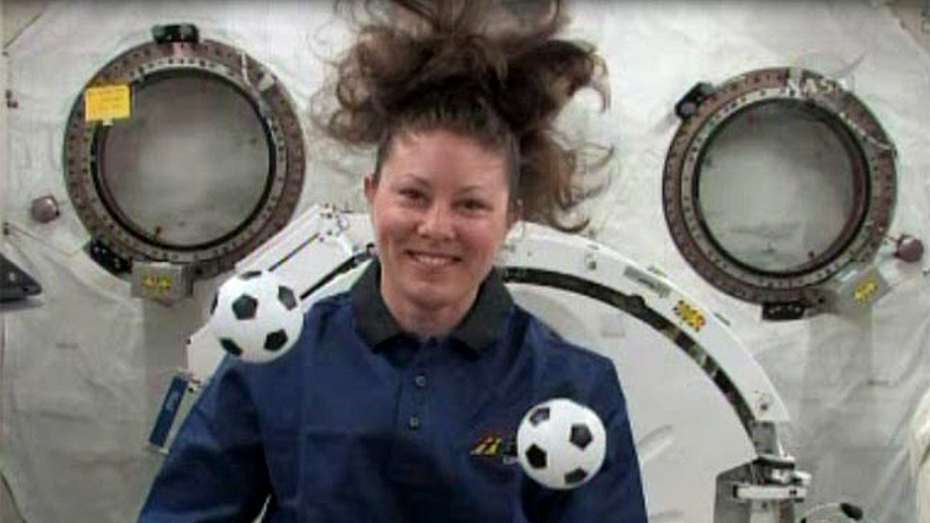 NASA astronaut Tracy Caldwell Dyson plays with mini soccer balls in the weightless environment of the International Space Station. She and her crewmates plan to cheer on the games at the 2010 World Cup international soccer tournament.