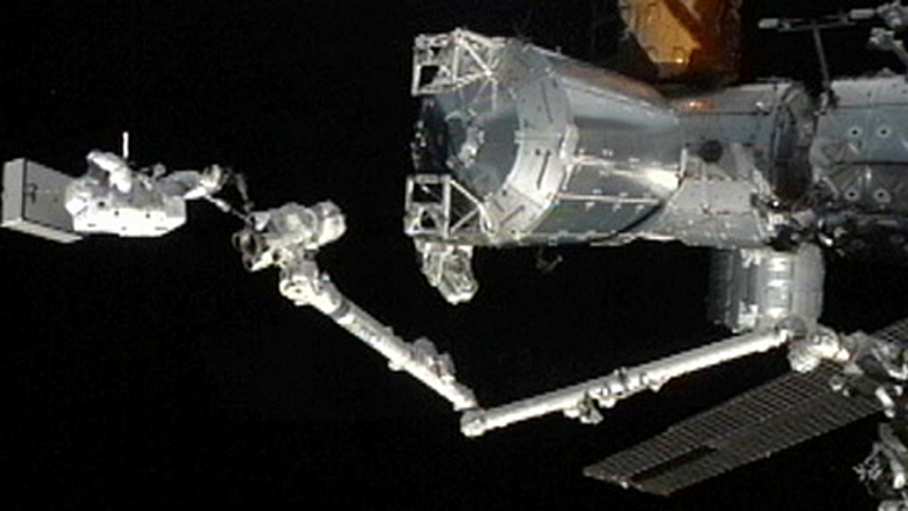 Japanese astronaut Akihiko Hoshides stands a the tip of the International Space Station's robotic arm during an Aug. 30, 2012, spacewalk outside the orbiting lab with crewmate Sunita Williams of NASA.