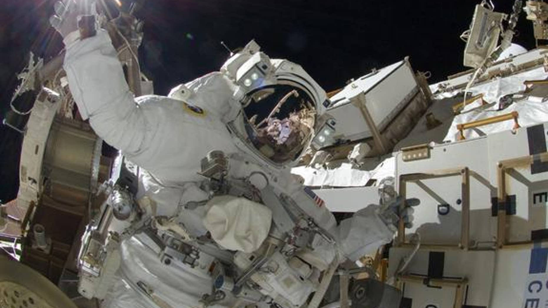 NASA astronaut Sunita Williams, Expedition 32 flight engineer, appears to touch the bright sun during the mission's third spacewalk on Sept. 5, 2012.