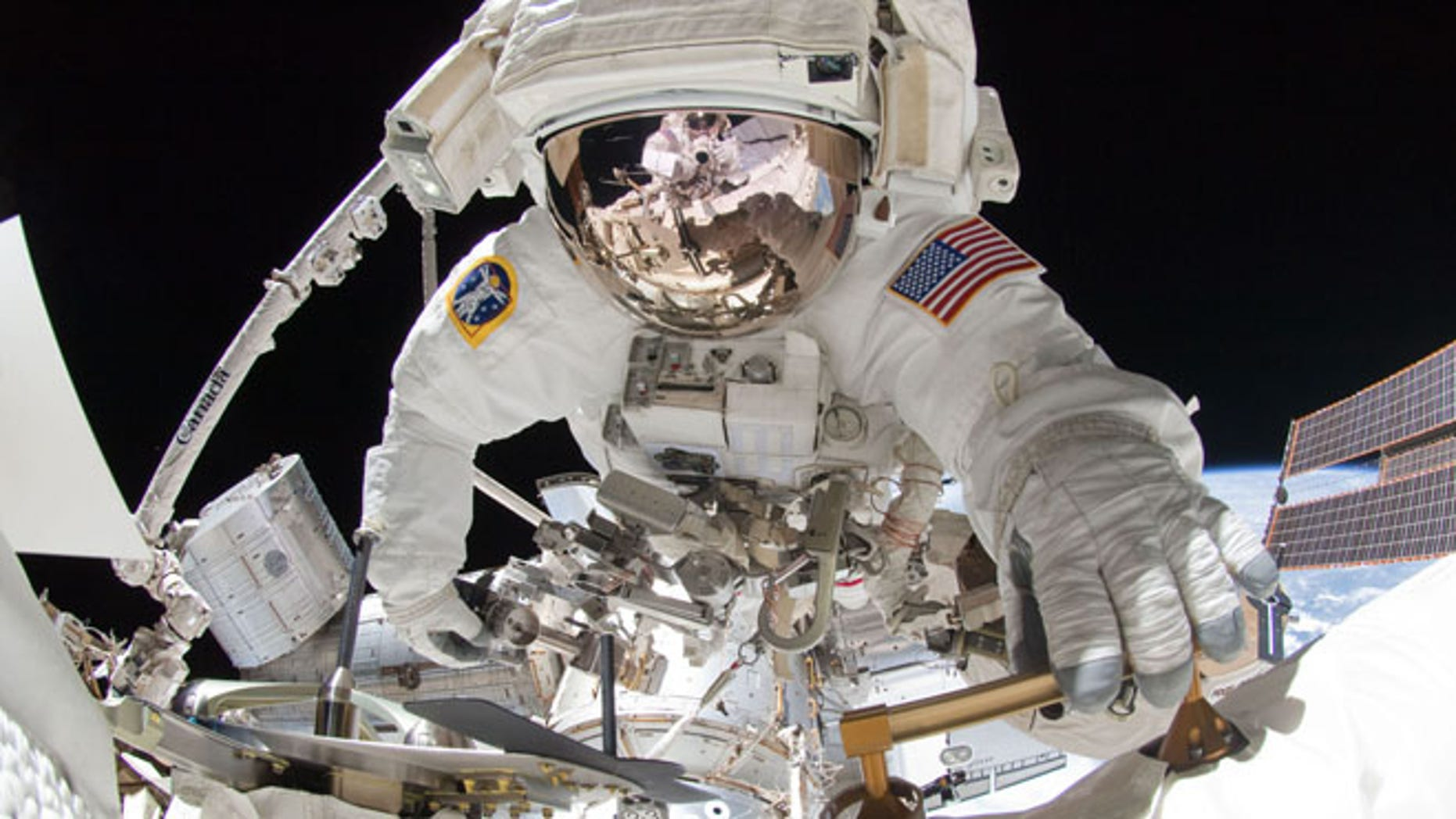 NASA astronaut Greg Chamitoff takes center stage in this amazing spacewalk photo taken by crewmate Mike Fincke (visible in the reflection on Chamitoff's spacesuit visor) using a fish-eye lens and digital camera during a May 27, 2011 excursion outside the International Space Station.
