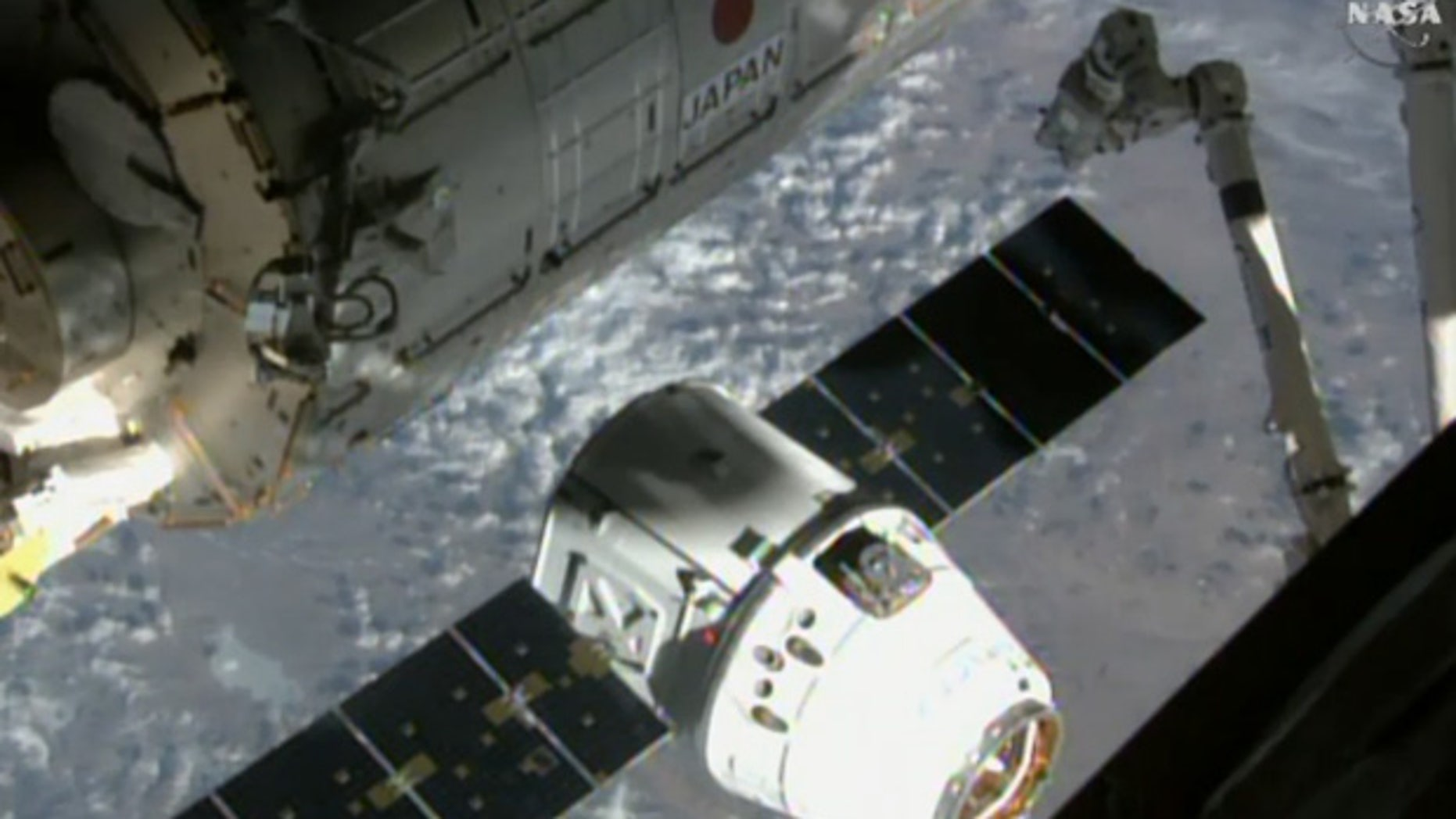 SpaceX's uncrewed Dragon cargo ship approaches the International Space Station (ISS) on April 17, 2015, in this still from a camera on the orbiting lab's exterior. This same Dragon arrived at the space station on Dec. 17, 2017.