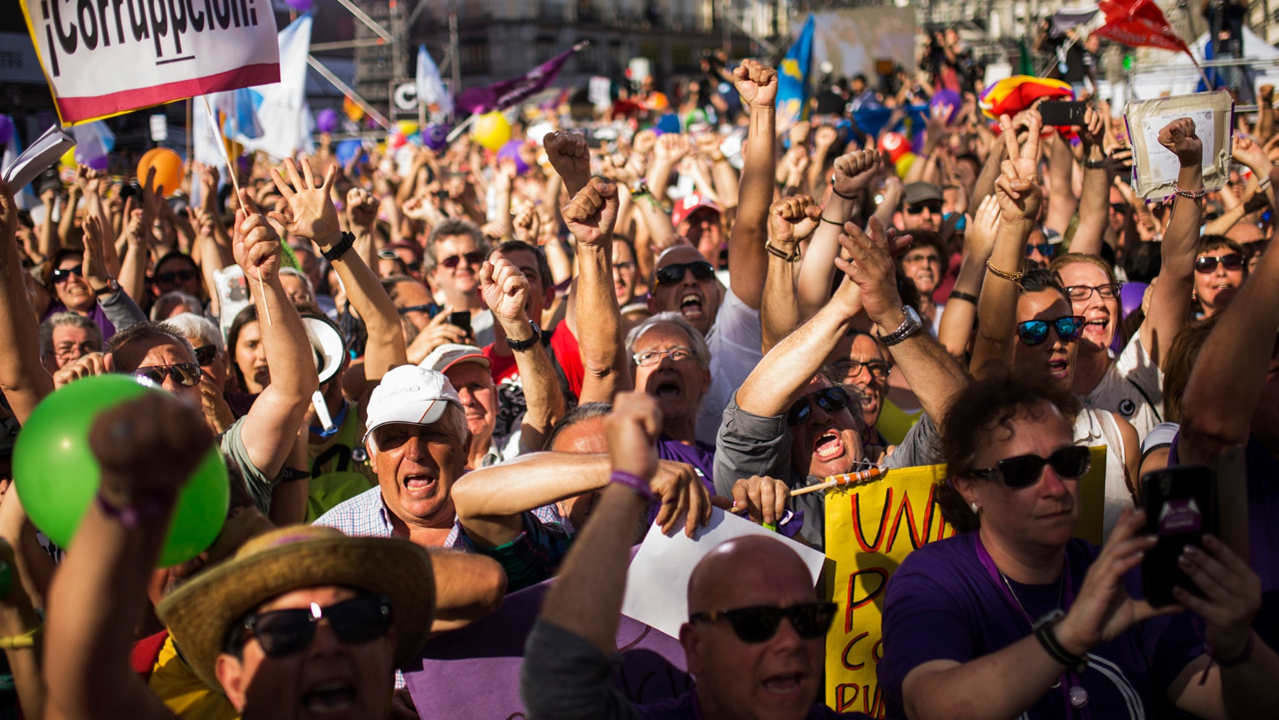 """People, one holding a placard reading in Spanish: """"Corruption"""", shout slogans during a rally in Madrid, Saturday, May 20, 2017."""