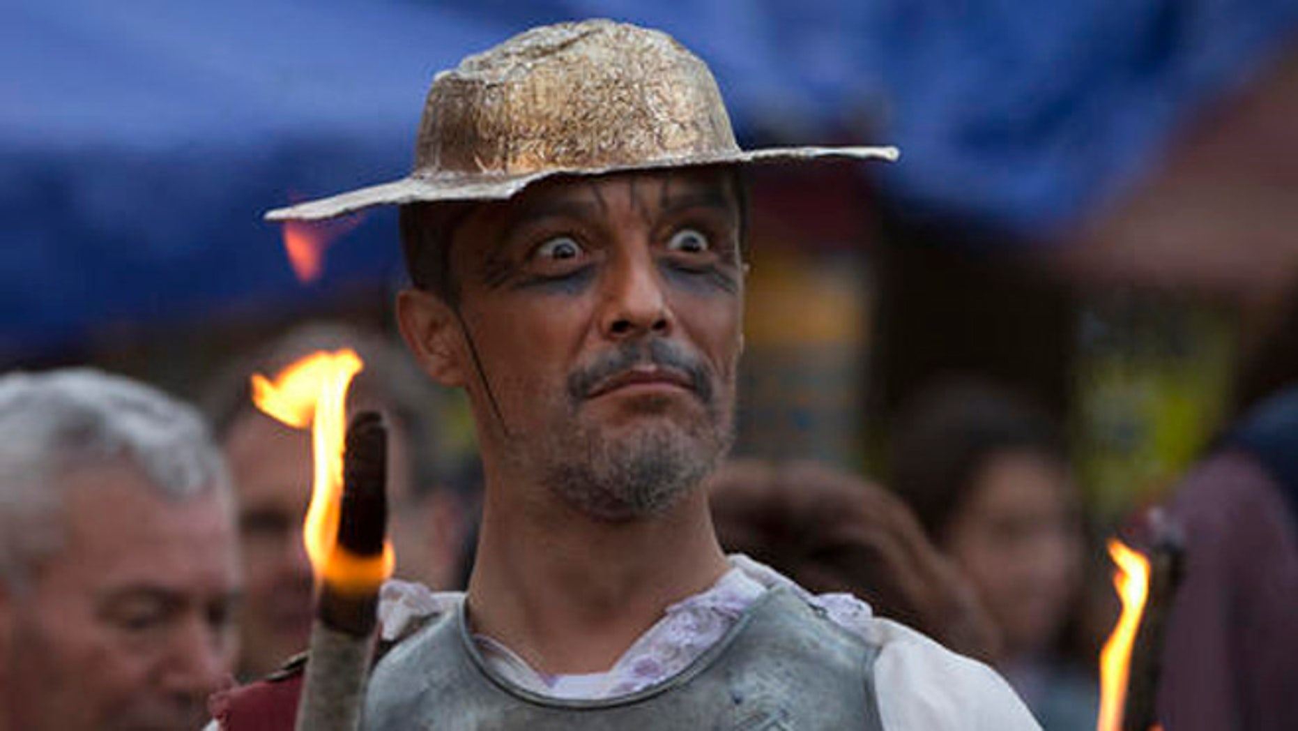 A man dressed as the character of Don Quixote holds a flaming stick during a mock funeral for Spanish writer Miguel de Cervantes, author of 'Don Quixote'  to commemorate the 400th anniversary of his death, in his birthplace of Alcala de Henares, Spain, Friday April 22, 2016. (AP Photo/Paul White)
