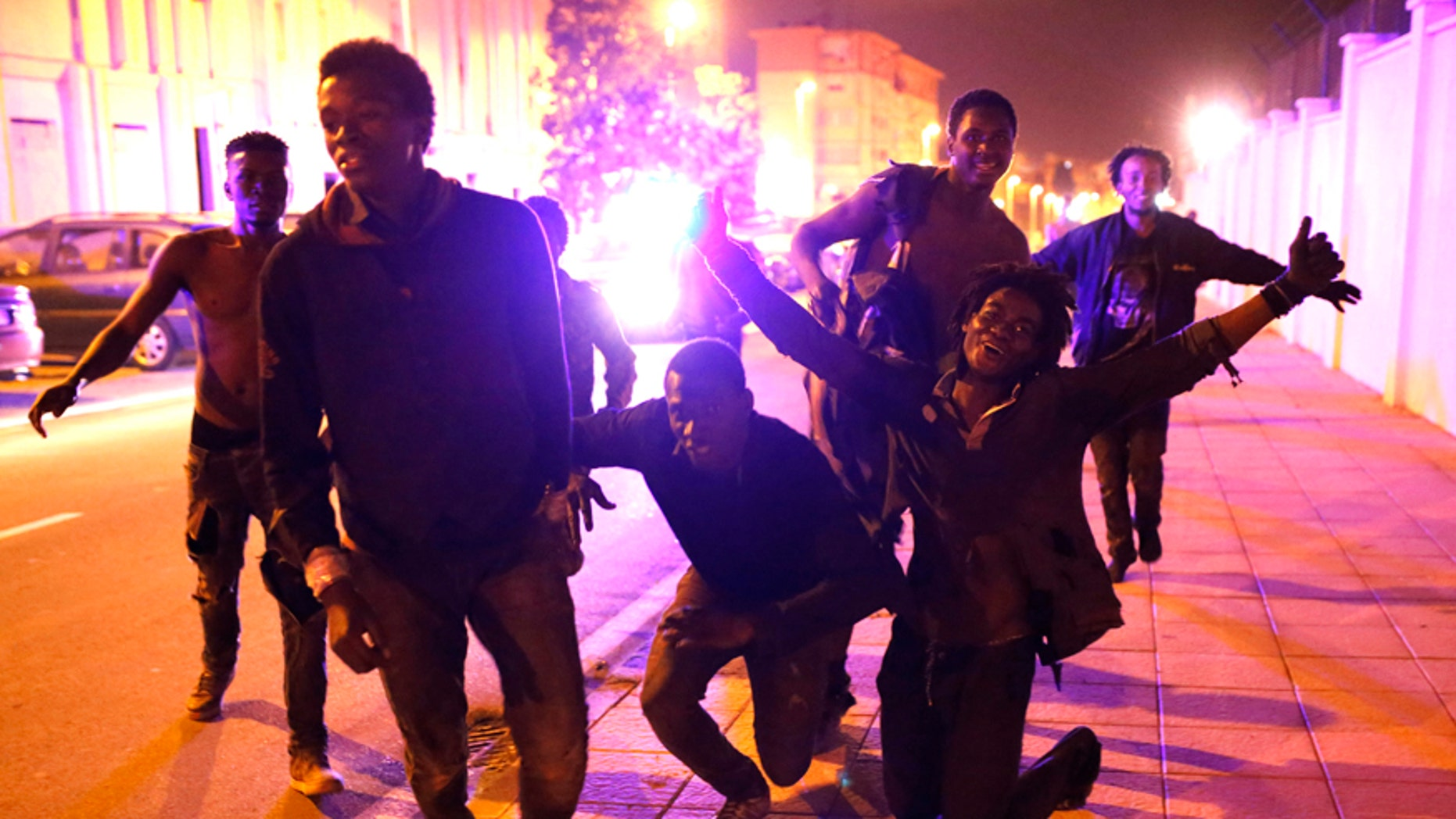 Migrants react after storming a fence to enter the Spanish enclave of Ceuta, Spain, Friday, Feb. 17, 2017.