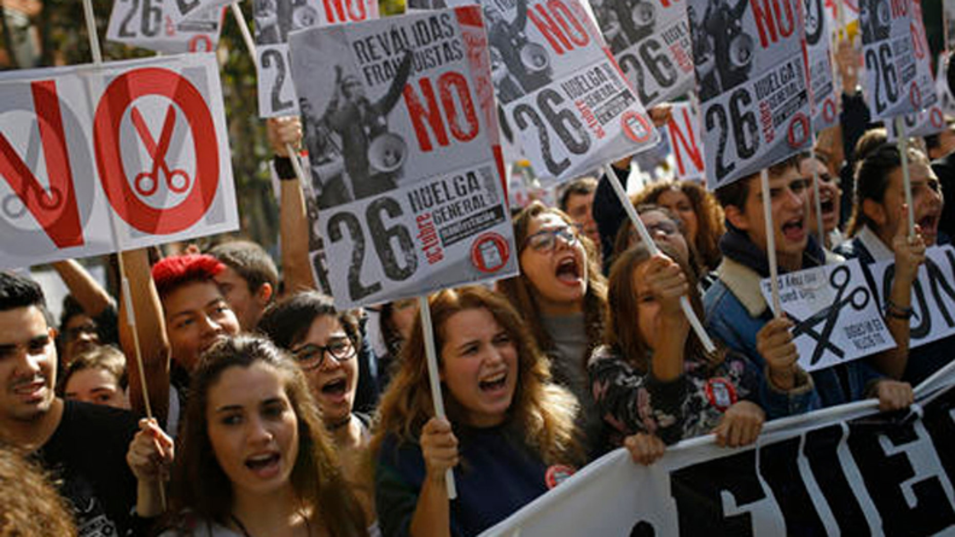 EDS NOTE : SPANISH LAW REQUIRES THAT THE FACES OF MINORS ARE MASKED IN PUBLICATIONS WITHIN SPAIN. High school student march during a demonstration in Madrid, Spain, Wednesday Oct. 26, 2016. The students who are on a one day strike are protesting about the country's education law that increases the number of annual exams. The education bill was brought in 2014 by the conservative Popular Party. Opposed by most other political parties and many teacher and parent groups, it increases the number of annual exams.The government claimed it was aimed at stemming Spain's school dropout rate. Banners read in Spanish; 'General Strike' and 'No to exam re-takes from the Franco era' . (AP Photo/Francisco Seco)