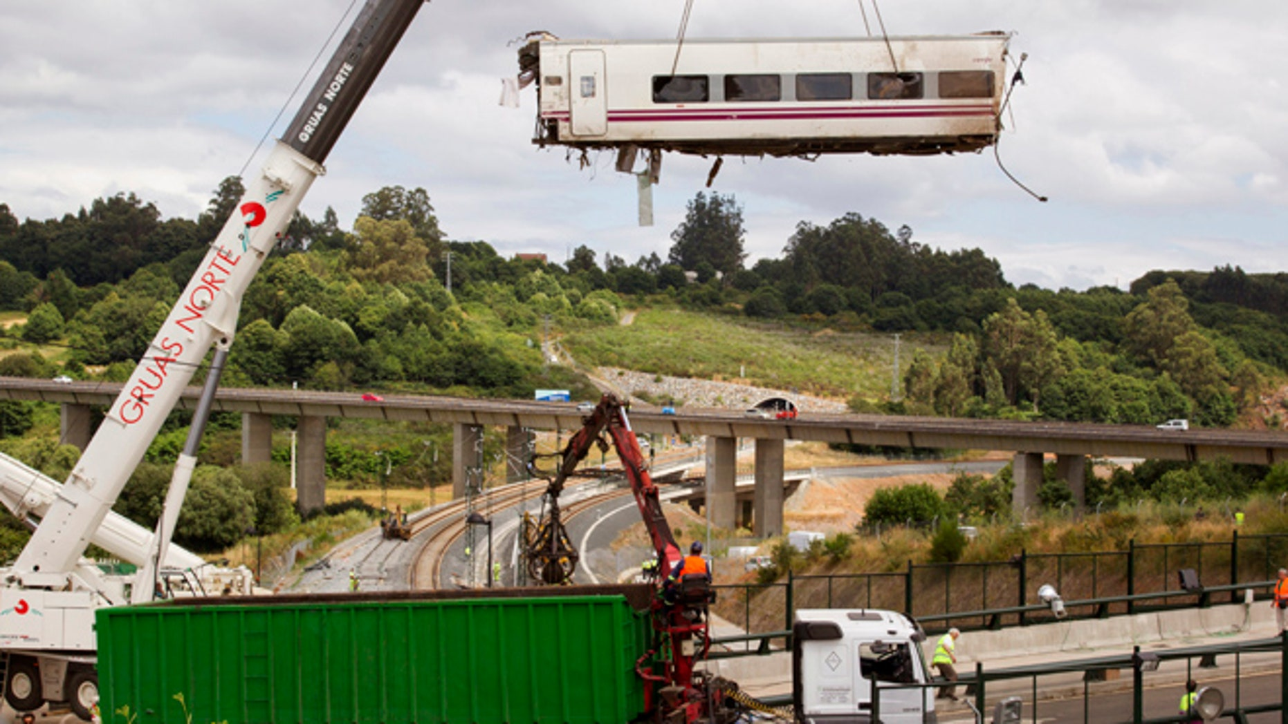 July 25, 2013: In this file photo, a derailed train car is lifted by a crane at the site of a train accident in Santiago de Compostela, Spain.