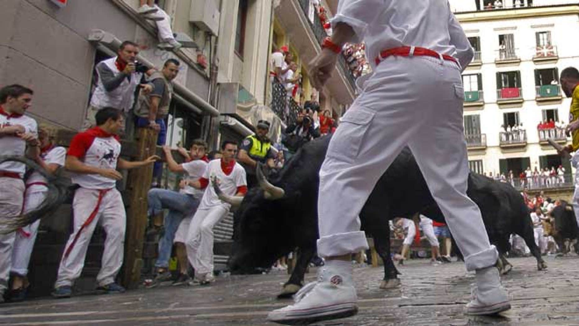 July 7, 2012: Revelers run on the Estafeta corner ahead of Dolores Aguirre Yabarra ranch bulls during the first running of the bulls at the San Fermin fiestas, in Pamplona northern Spain