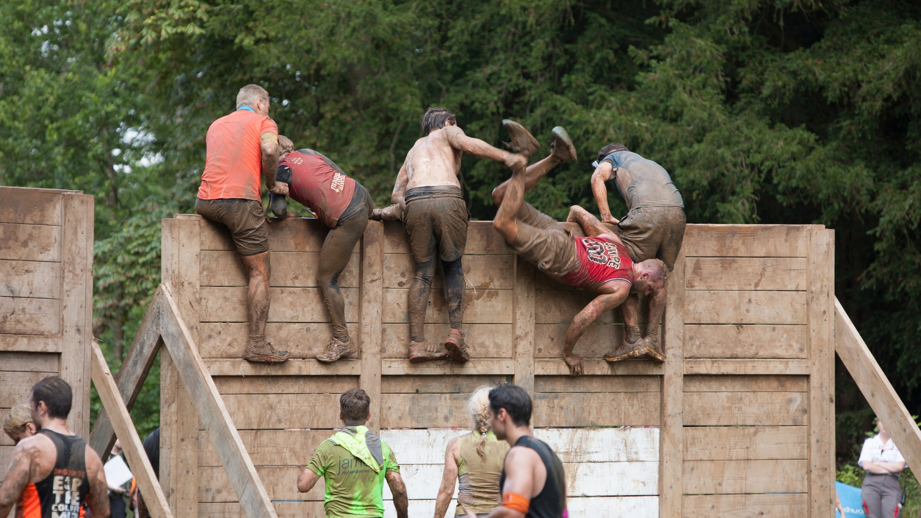 A group of people help each other tackle a high wooden barrier on their gruelling 12 mile assault course during the 'Tough Mudder' challenge in Cirencester park, Gloucestershire. This annual event is a team-based 10-12 mile obstacle course designed to test physical strength endurance.