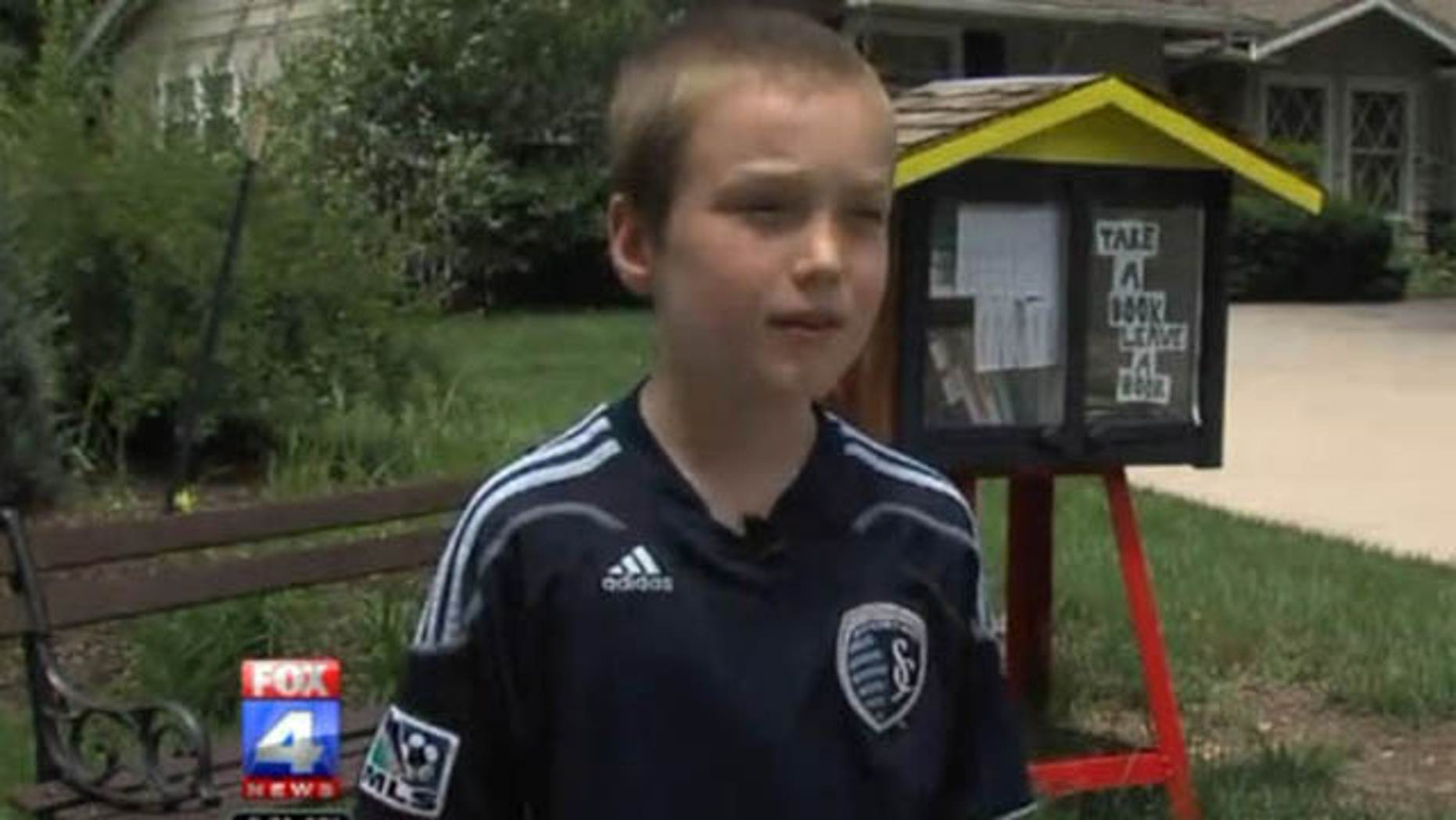 This photo shows 9-year-old Kansas City boy Spencer Collins with his outdoor library (Courtesy WDAF-TV)