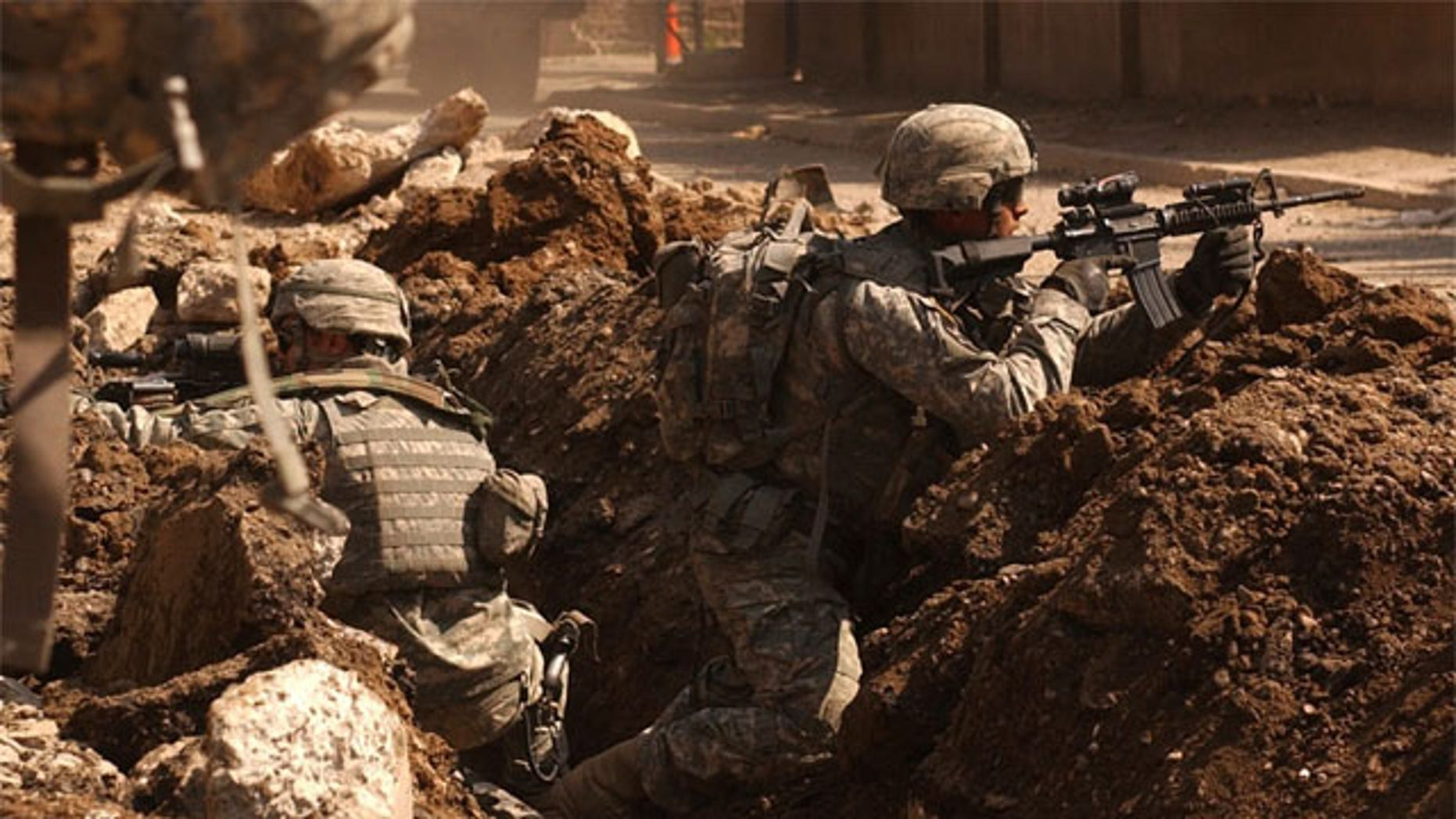 Soldiers occasionally get a sixth sense feeling about battlefield dangers. Here, Sgt. Auralie Suarez and Pvt. Brett Mansink take cover during a firefight with anti-Iraqi forces in the Al Doura section of Baghdad, March 7.