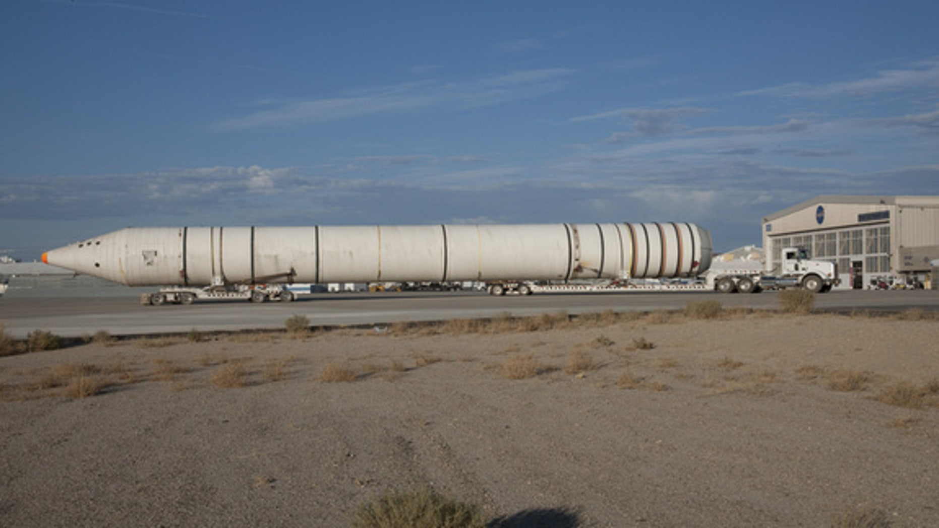 Mounted on special lowboy trailer dollies, one of the two space shuttle solid rocket boosters is hauled up the ramp from Rogers Dry Lake after arrival at NASA's Dryden Research Center in California.