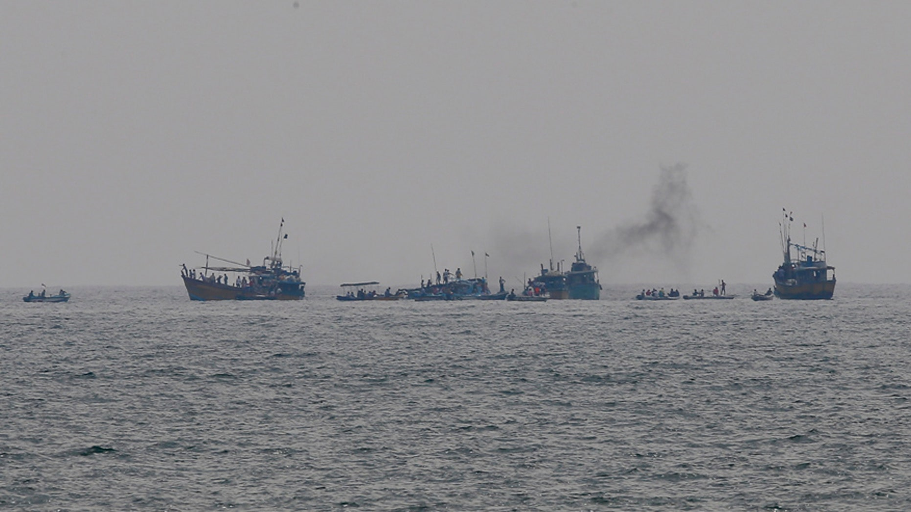 Sri Lanka's navy and rescue boats are seen engaged in rescue operation after a boat capsized in the Indian Ocean off the country's southwestern coast in Beruwala, 60 kilometers (37 miles) south of Colombo, Sri Lanka, Sunday, Feb. 19, 2017. (AP Photo/Eranga Jayawardena)