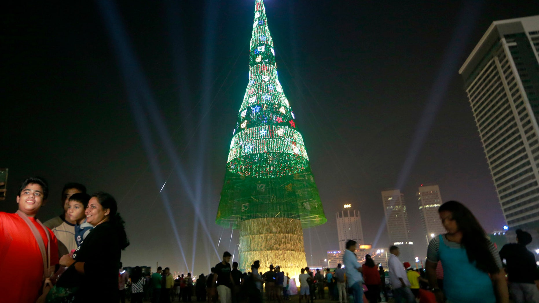 A Sri Lankan family takes photographs standing near an enormous artificial Christmas tree as others gather around it in Colombo, Sri Lanka, Saturday, Dec. 24, 2016.