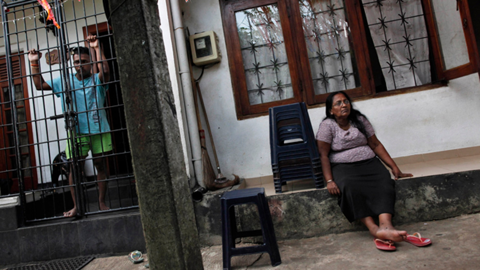 May 7, 2012: Ravindra Udayashantha, left, a 38-year-old town council chairman looks through iron bars guarding the entrance to his house, as his mother Rupawathi Perera sits outside in Kolonnawa, suburb of Colombo, Sri Lanka.