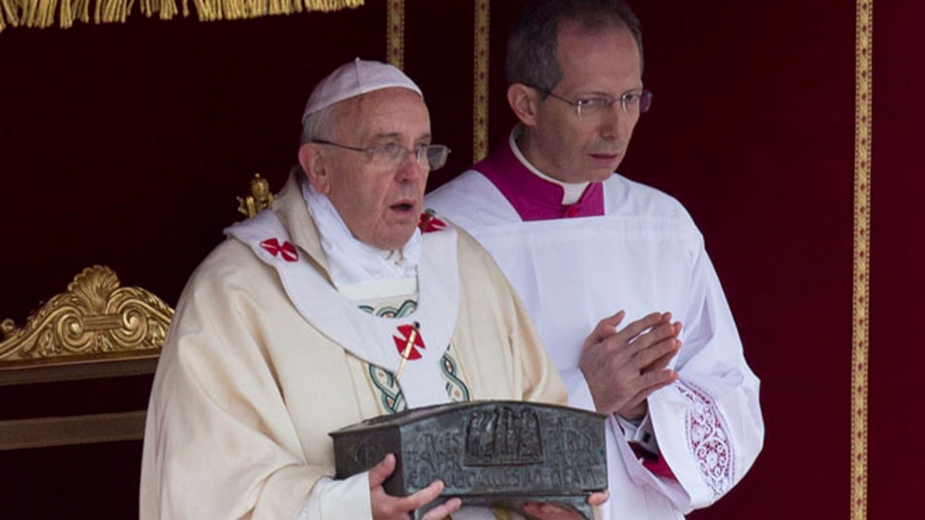 Nov. 24, 2013: Pope Francis, left, holds the relics of St. Peter as he celebrates mass for the end of the Year of Faith, in St. Peter's Square at the Vatican.