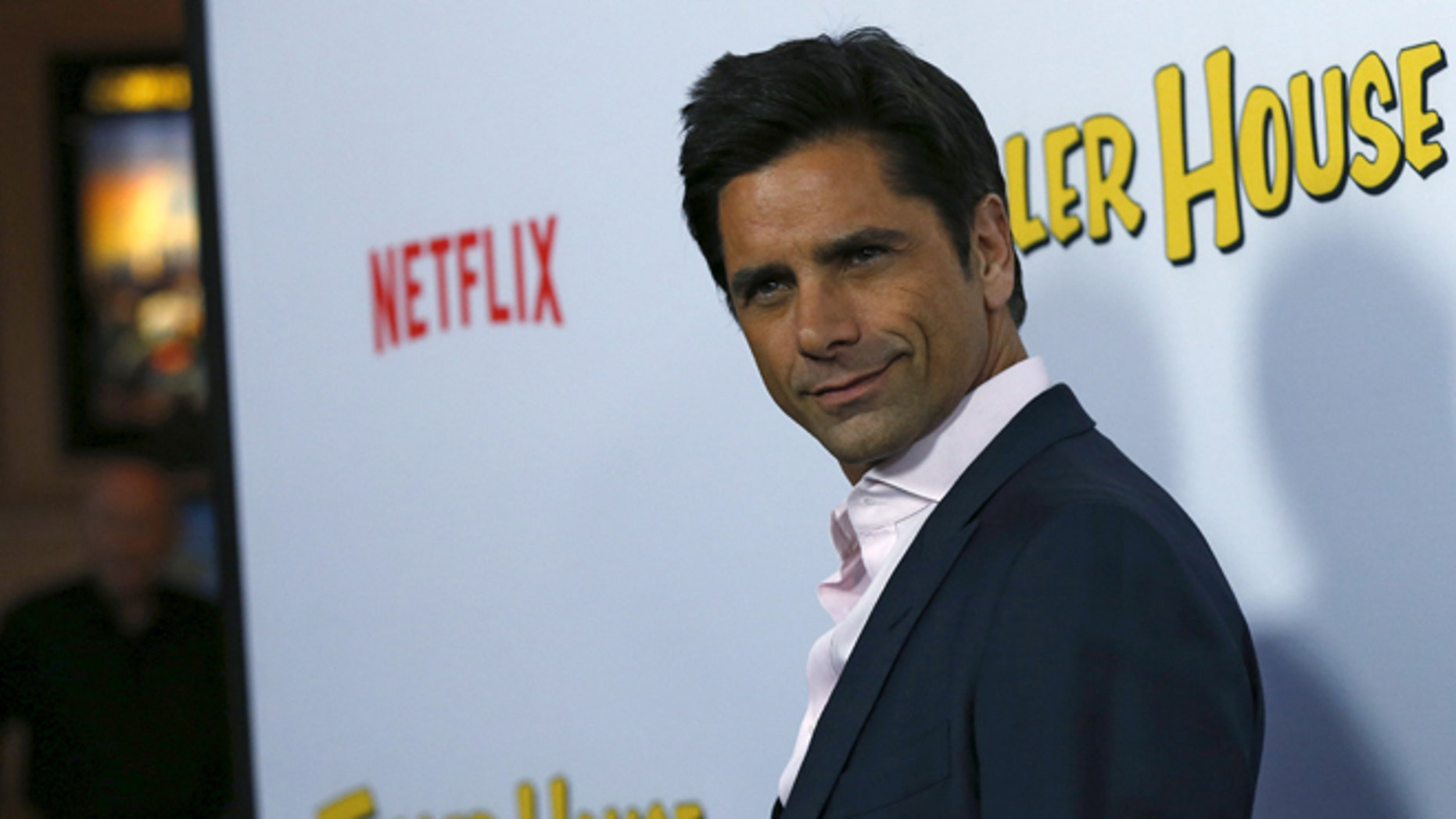 """February 16, 2016. John Stamos poses at the premiere for the Netflix television series """"Fuller House"""" in Los Angeles."""