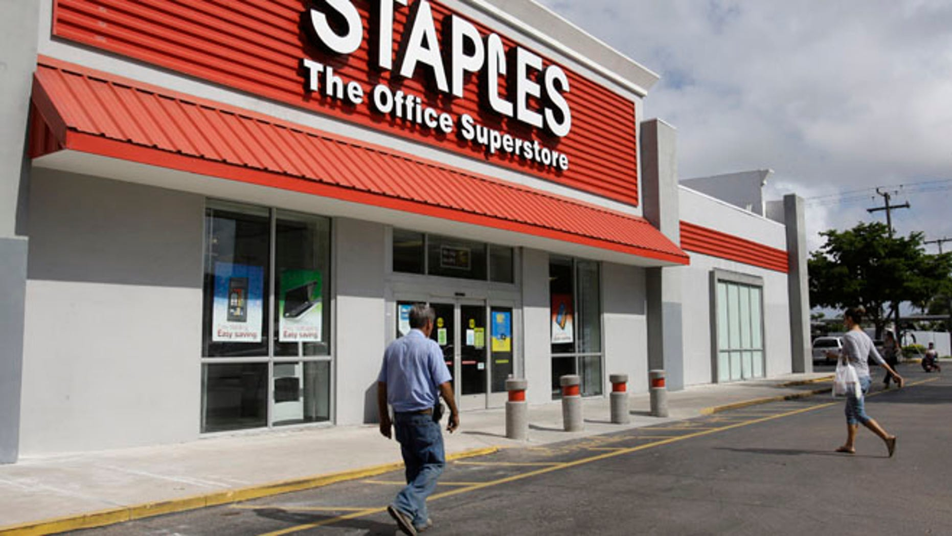 This March 6, 2013 file photo shows a Staples office supply store Miami. The opening of Postal Service retail centers in dozens of Staples stores around the country is being met with threats of protests and boycotts by the agencys unions. The new outlets are staffed by Staples employees, not postal workers, and labor officials say that move replaces good-paying union jobs with low-wage, nonunion workers.