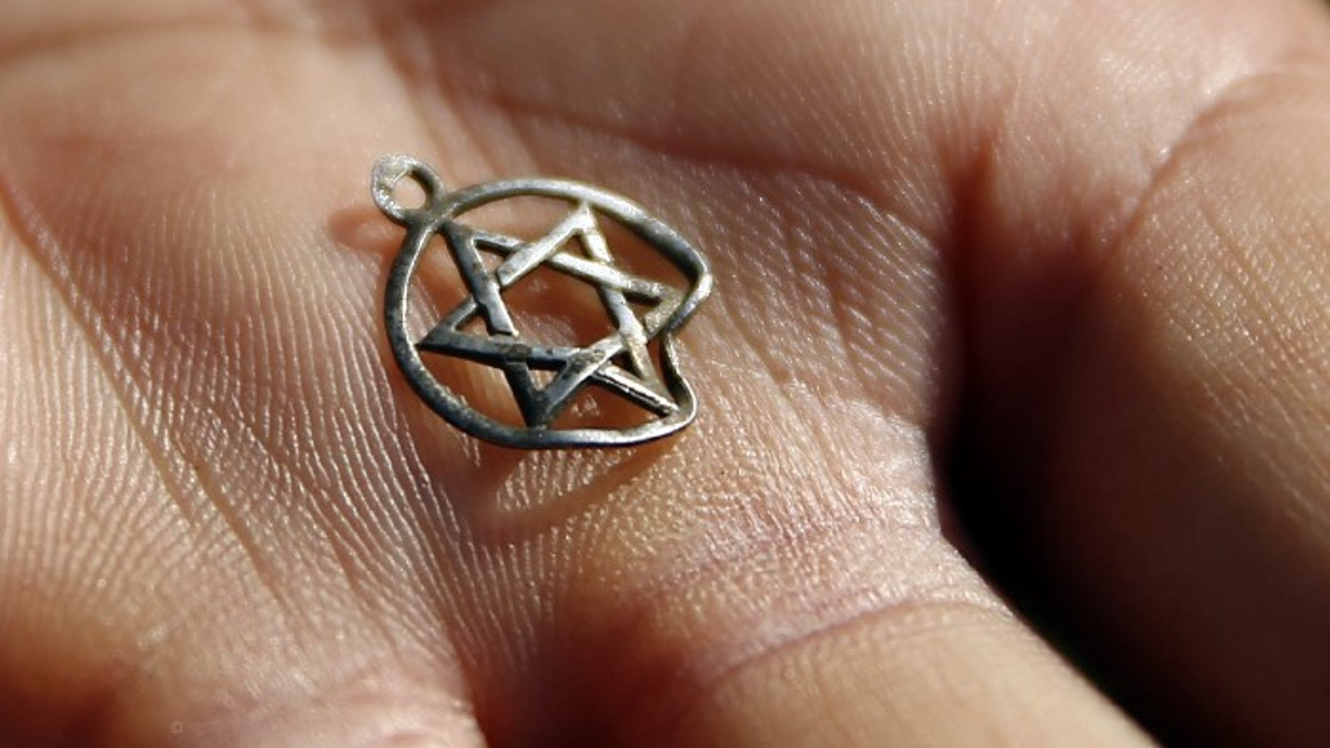FILE -- A medallion in the shape of the Star of David is shown after being discovered in the perimeter of a Nazi death camp in Sobibor September 18, 2014.
