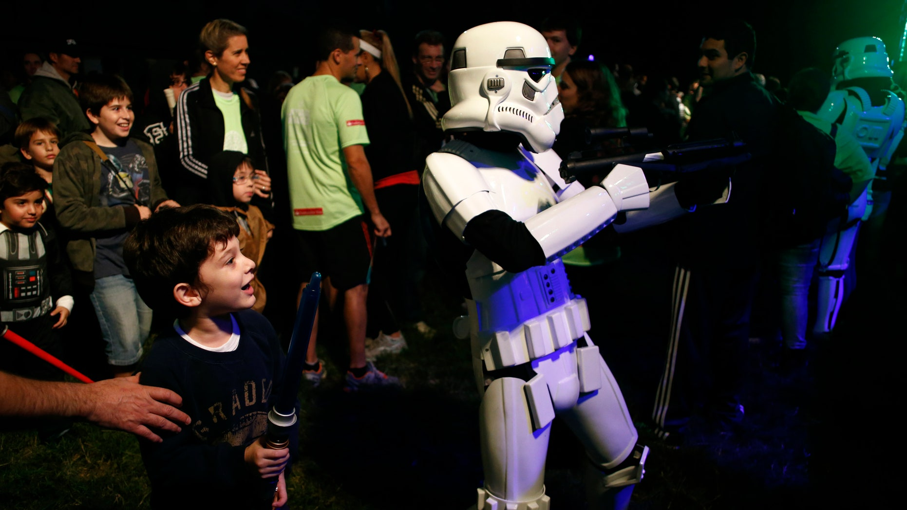 May 3, 2014. A boy looks at a man dressed as a stormtrooper from the Star Wars movies before the Star Wars Run race ahead of Star Wars Day in Buenos Aires.