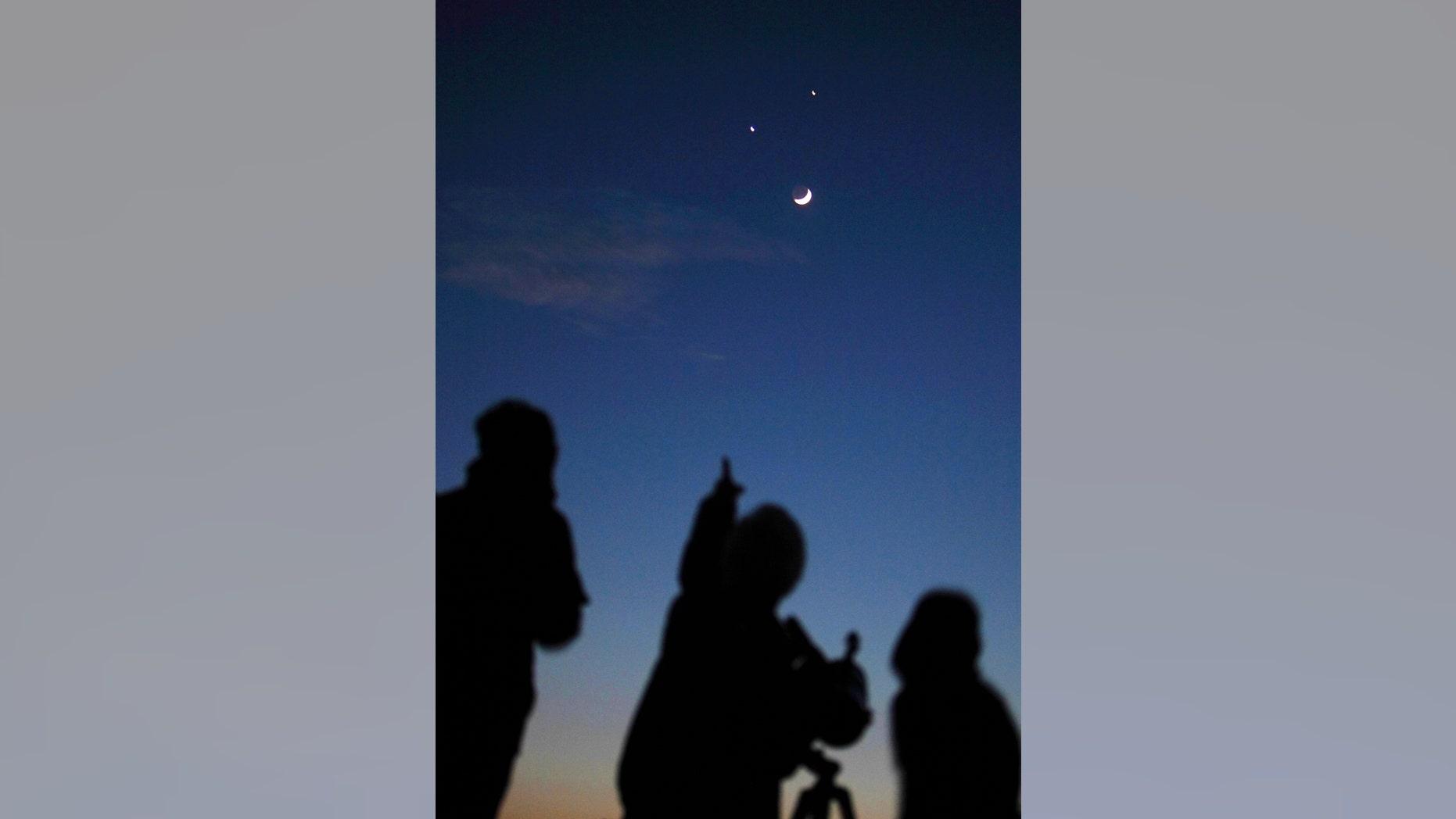 Star gazers look at the crescent moon below Jupiter (top) and Venus in Kathmandu December 1, 2008. (REUTERS/Gopal Chitrakar)