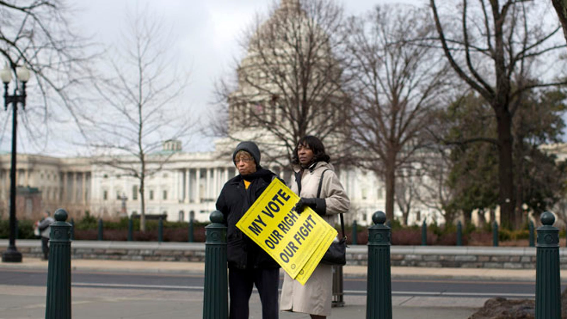 FILE: Feb. 27, 2013: People standing outside the Supreme Court in Washington before the start of a rally during arguments in the Shelby County, Ala., v. Holder case.