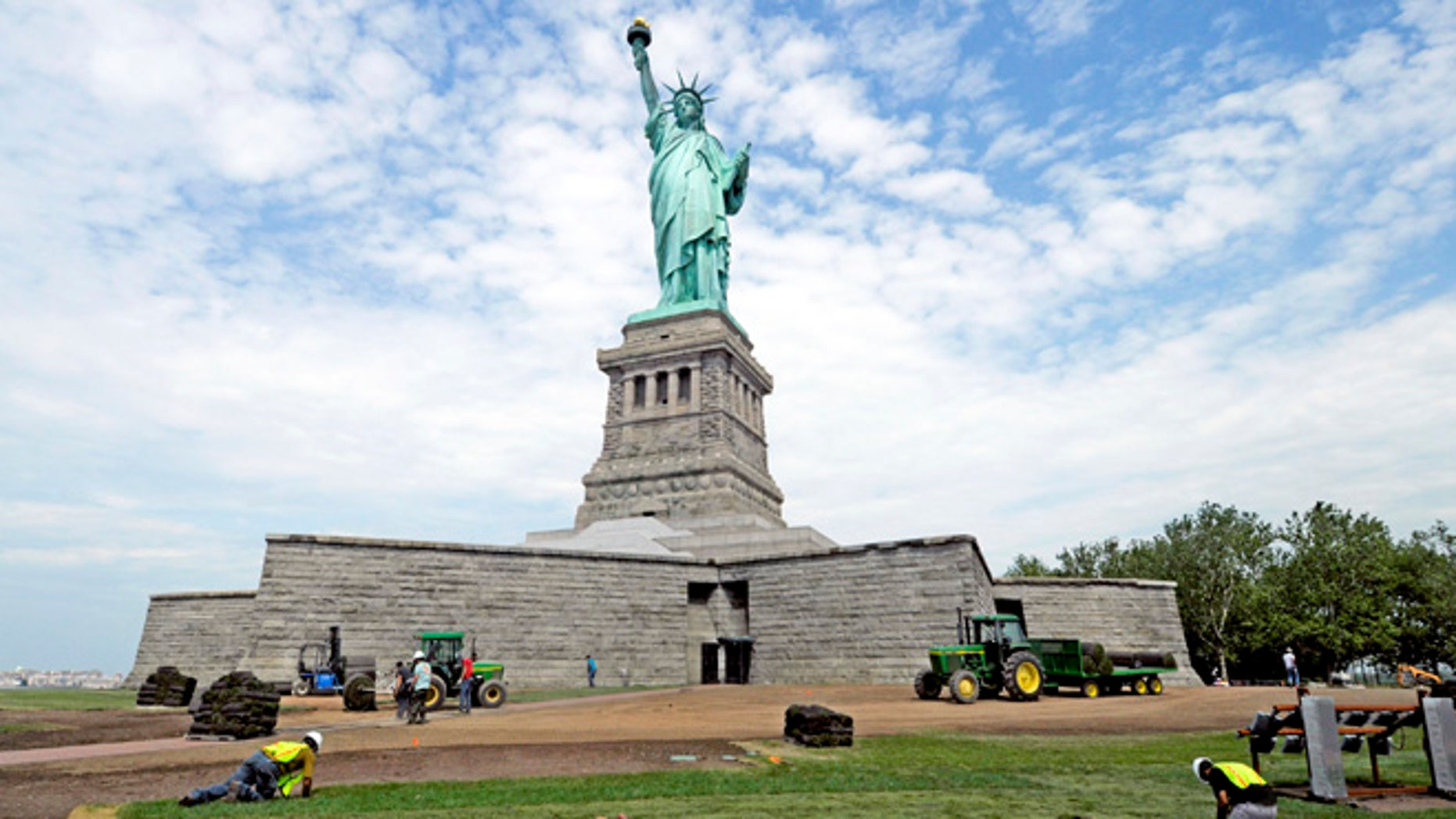 June 26, 2013: In this photo provided by the National Park Service, workers on Liberty Island install sod around the national monument which is set to re-open on the 4th of July, in New York. Months after railings broke, docks and paving stones were torn up and buildings were flooded by Superstorm Sandy, the Statue of Liberty will finally welcome visitors again.