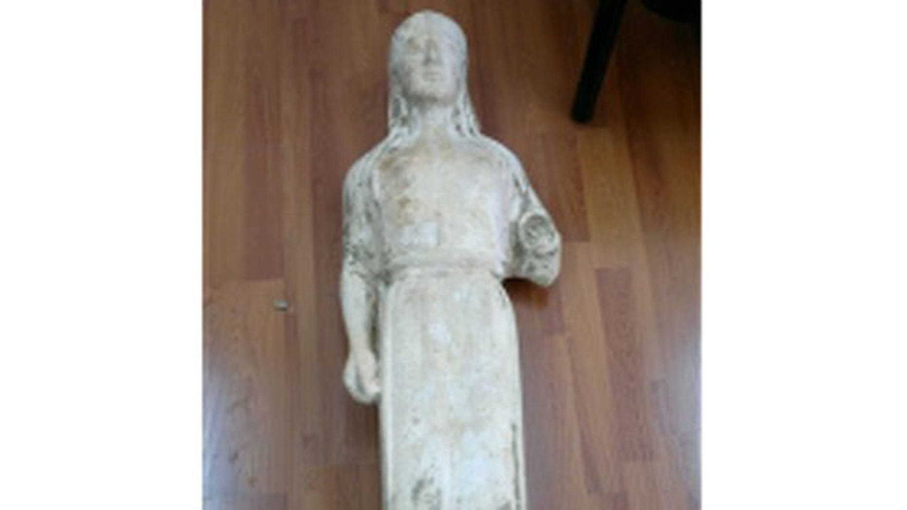 March 28, 2012: A 2,500-year-old statue of a young woman that was illegally excavated and hidden in a goat-pen near Athens is seen in this police handout photo.