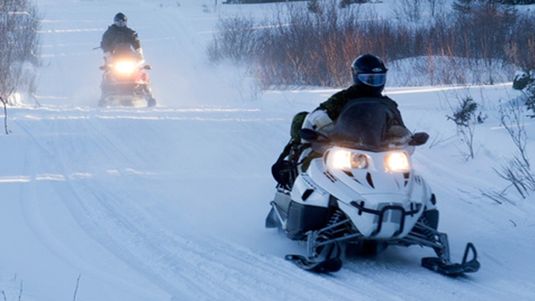 Members of the Arctic Response Company Group conducting exercises on conventional snow mobiles.