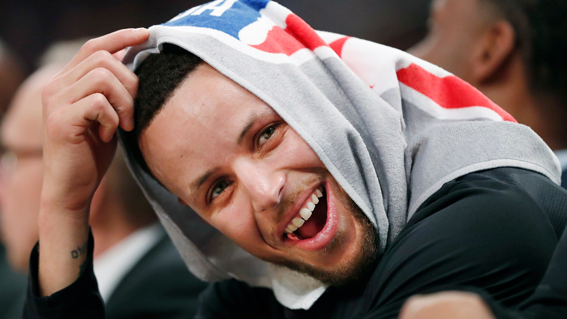 Golden State Warriors guard Stephen Curry, his head covered by a towel, laughs with teammates during the second half of an NBA basketball game against the New York Knicks, Monday, Feb. 26, 2018, in New York.