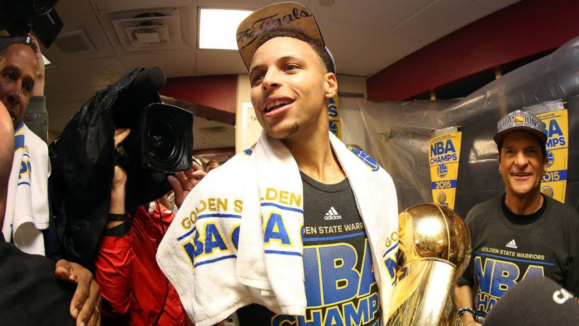 CLEVELAND, OH - JUNE 16: Stephen Curry #30 of the Golden State Warriors celebrates with the Larry O'Brien NBA Championship Trophy in the locker room after they defeated the Cleveland Cavaliers 105 to 97 in Game Six of the 2015 NBA Finals at Quicken Loans Arena on June 16, 2015 in Cleveland, Ohio. NOTE TO USER: User expressly acknowledges and agrees that, by downloading and or using this photograph, user is consenting to the terms and conditions of Getty Images License Agreement. (Photo by Ezra Shaw/Getty Images)