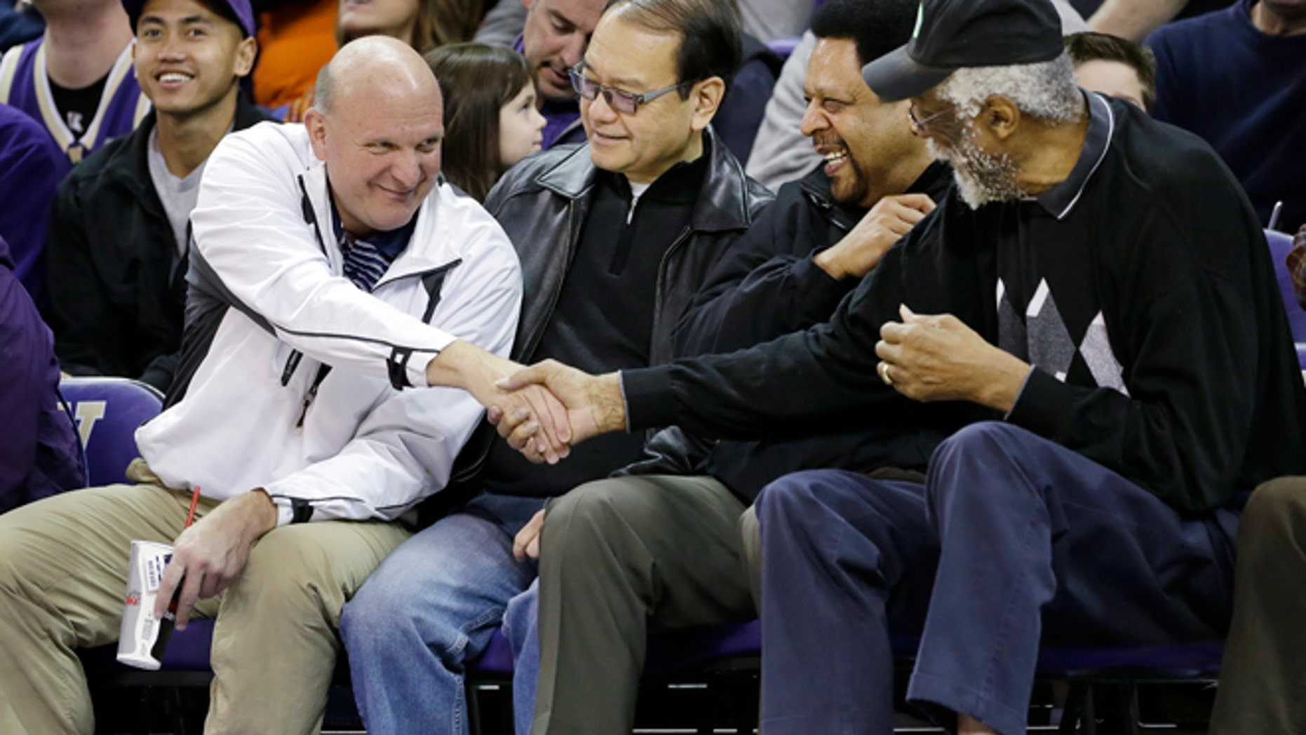 """Jan. 25, 2014: In this file photo, then-Microsoft CEO Steve Ballmer, left, shakes hands with former NBA players Bill Russell, right, and """"Downtown"""" Freddie Brown as Omar Lee looks on during an NCAA college basketball game between Washington and Oregon State in Seattle."""