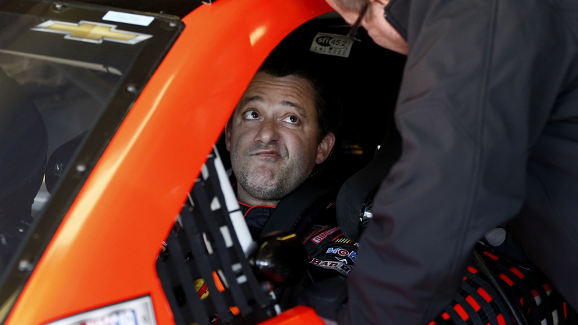 Driver Tony Stewart talks with a crew member as they get ready  to practice for Sunday's NASCAR Sprint Cup series auto race at the Texas Motor Speedway in Fort Worth, Texas, Saturday, Nov. 1, 2014. AP Photo/Jim Cowsert)