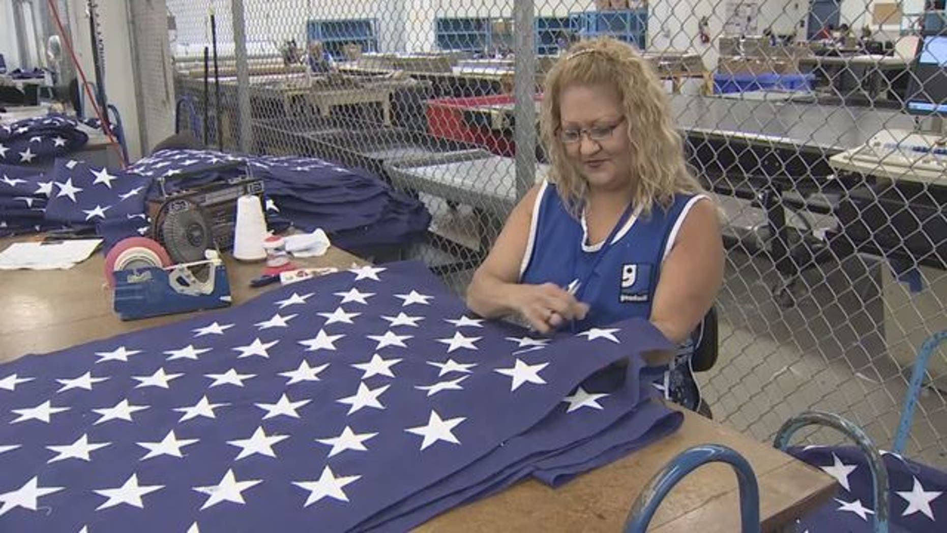 Goodwill employee works on flag at Goodwill Flag Center in South Florida. (WSVN)