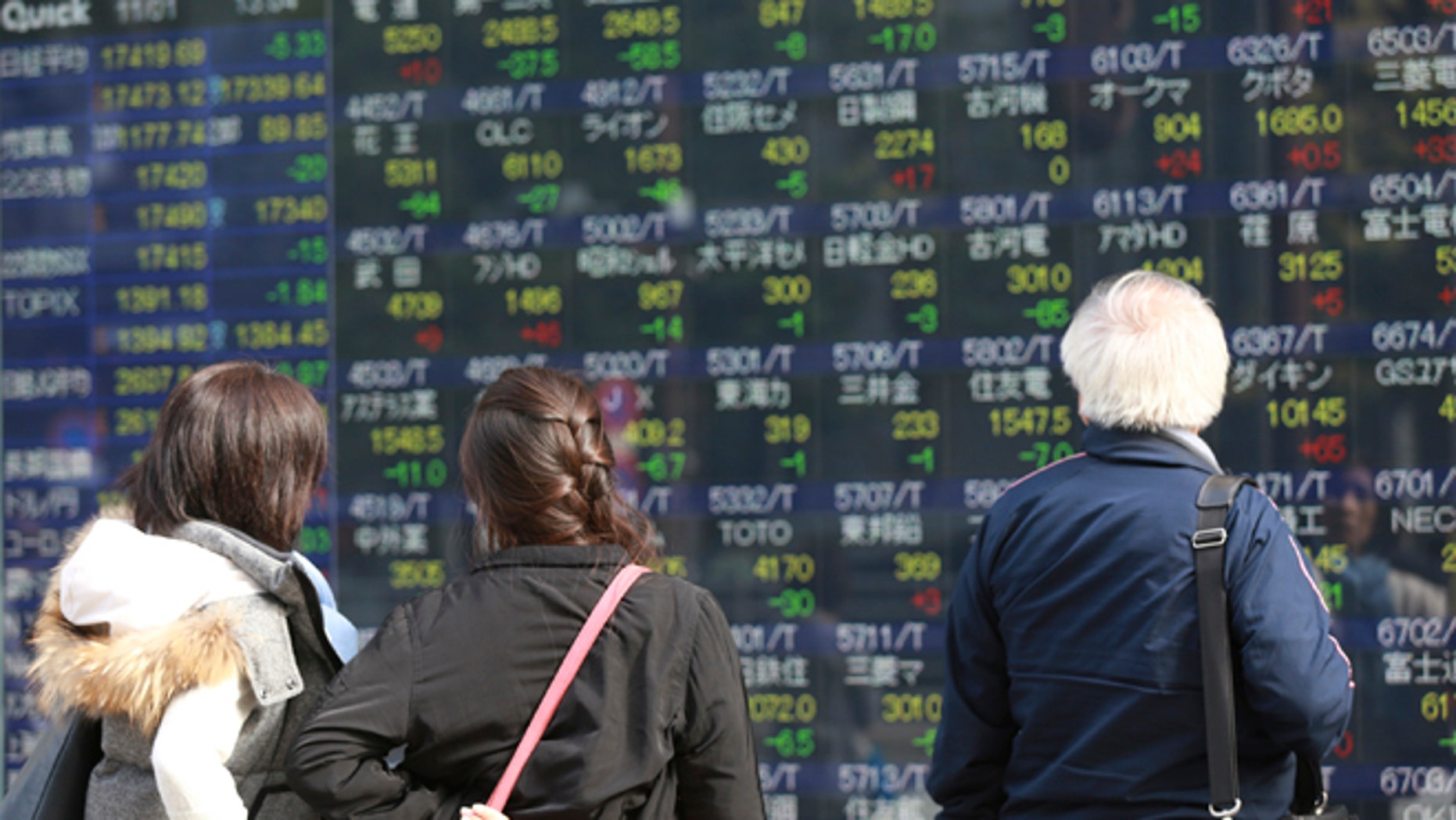 Pedestrian look at an electronic stock board of a securities firm in Tokyo, Tuesday, Nov. 1, 2016. Stocks indexes in Asia were mostly higher Tuesday after surveys showed China's factory activity rose to a two-year high last month, suggesting the world's No. 2 economy is stabilizing. (AP Photo/Eugene Hoshiko)