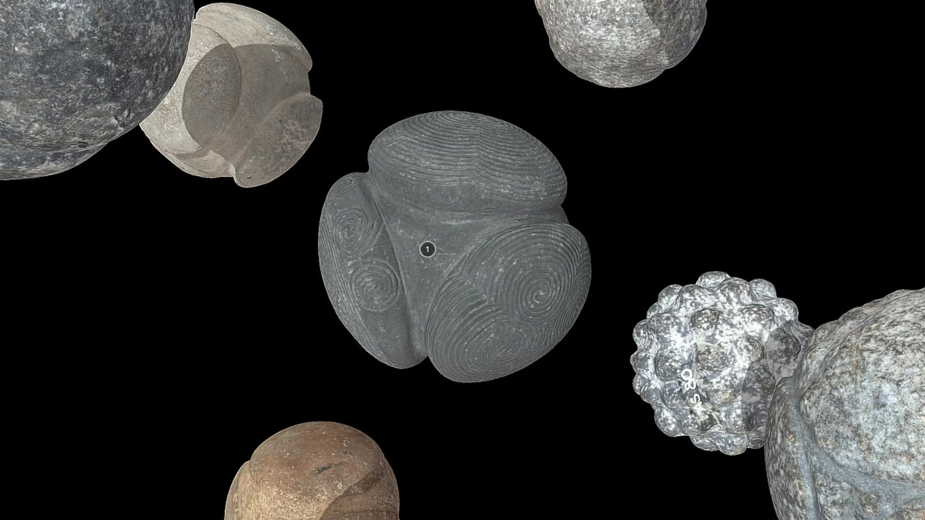 The 3D models of the carved balls of stone, including the spiral-carved Towie ball (center), are now posted online. Credit: National Museums Scotland