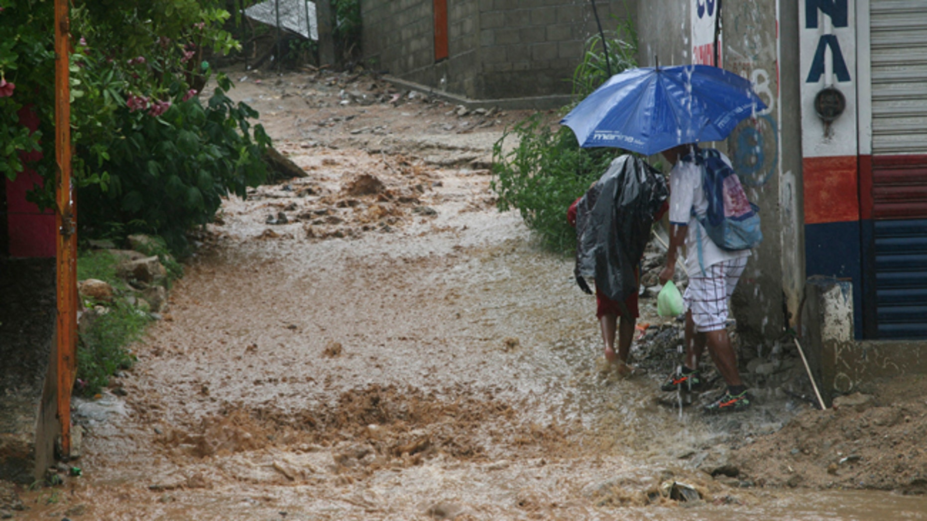 People walk under a downpour on a flooded street in Acapulco, Mexico, Thursday, Sept. 14, 2017.