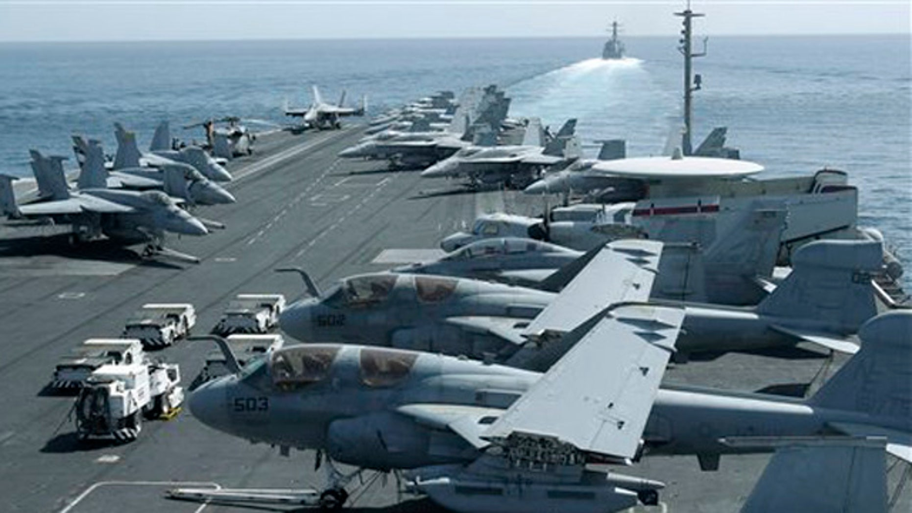 Feb. 14, 2012: A photo taken from the bridge of the Nimitz-class aircraft carrier USS Abraham Lincoln (CVN 72) shows US aircraft parked on the flight deck of a US destroyer, background, patrols the Arabian sea in the Strait of Hormuz.