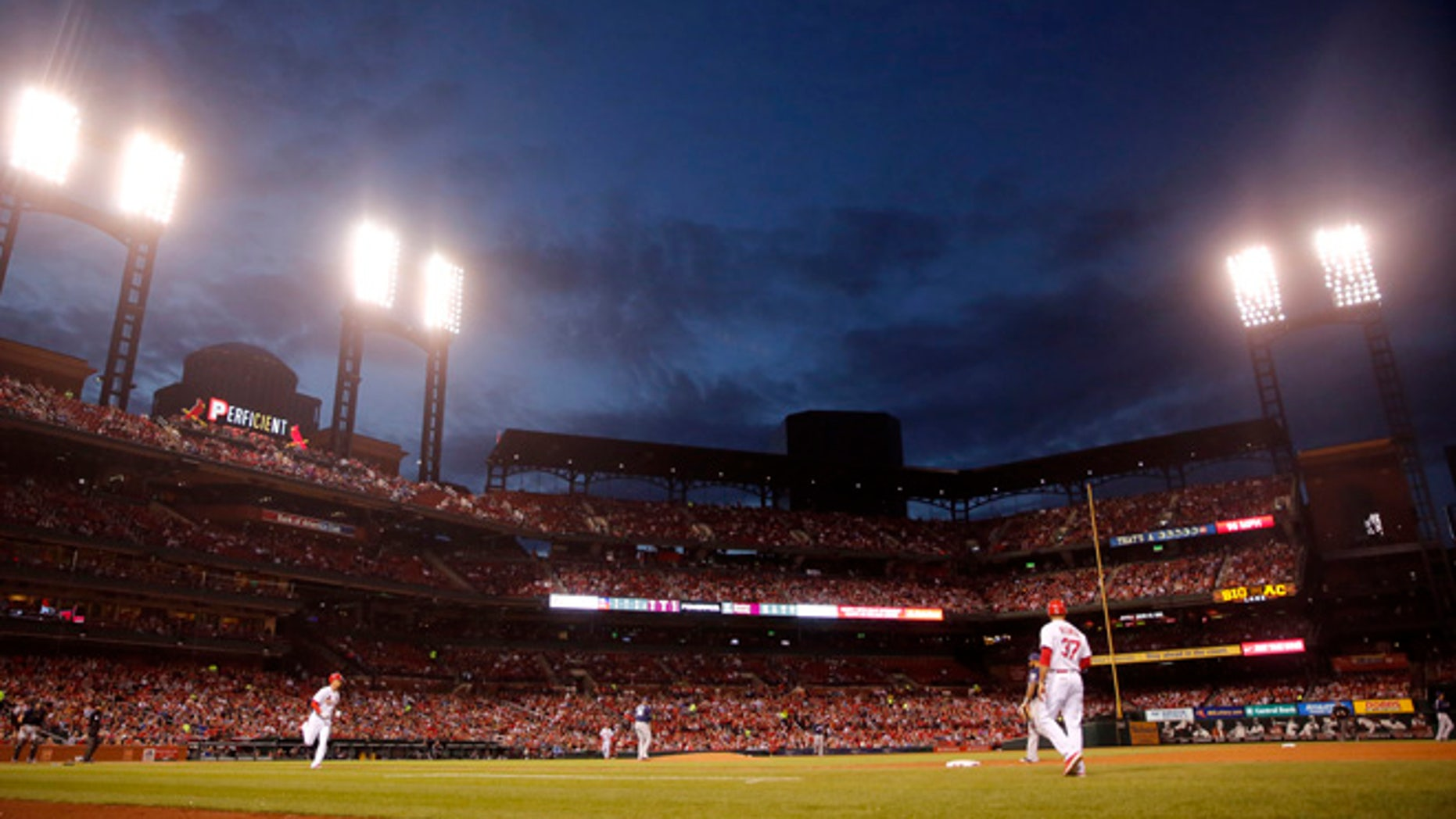 St. Louis Cardinals' Stephen Piscotty heads to first on a single as dusk falls over Busch Stadium during the fourth inning of a baseball game against the Milwaukee Brewers Tuesday, May 2, 2017, in St. Louis. (AP Photo/Jeff Roberson)