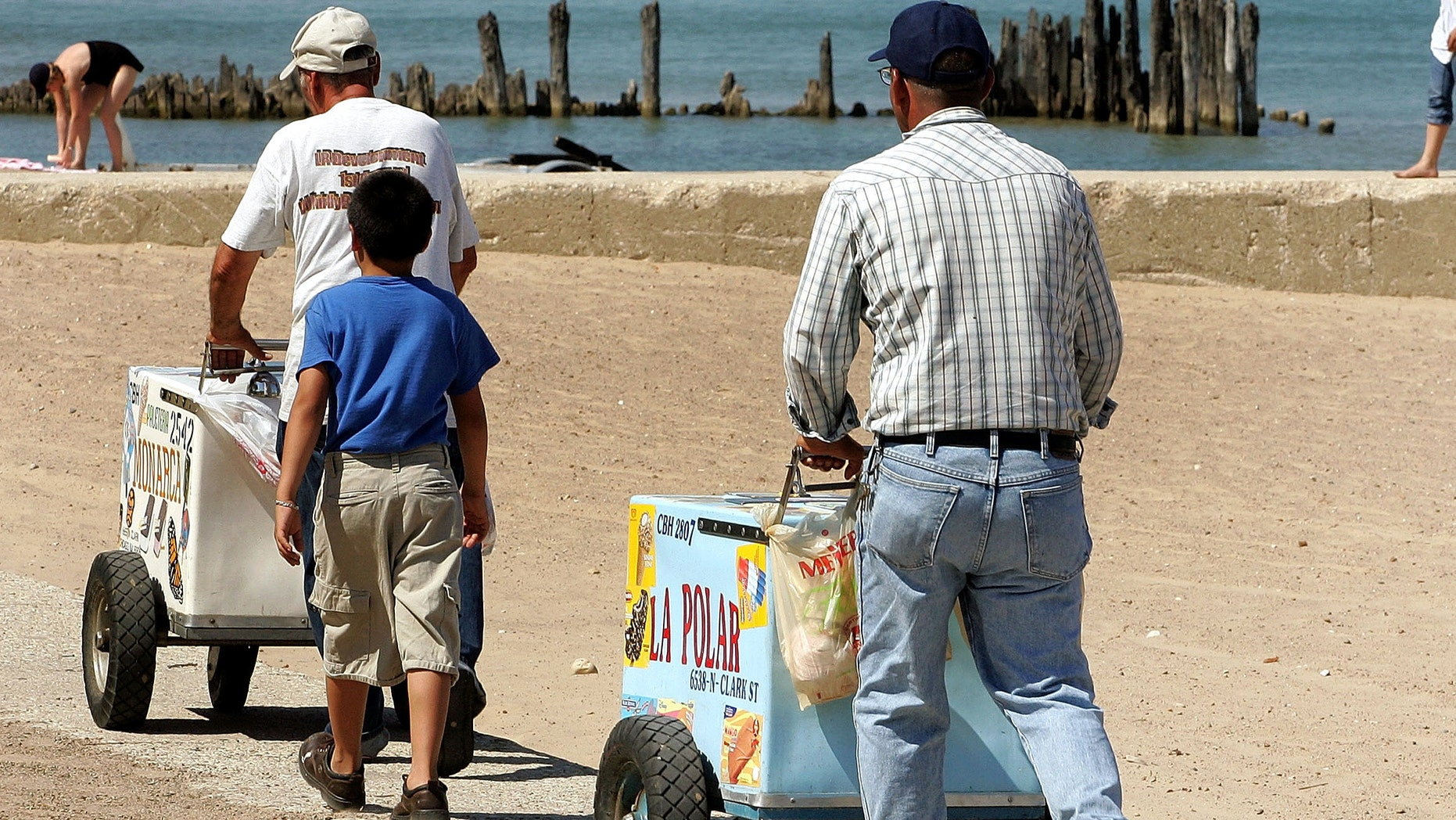 CHICAGO - JULY 24: Ice cream vendors push their carts on a beach along Lake Michigan July 24, 2005 in Chicago, Illinois. Extreme hot weather has hit several parts of the nation with highs over 100 degrees predicted in the Chicago area. (Photo by Tim Boyle/Getty Images)
