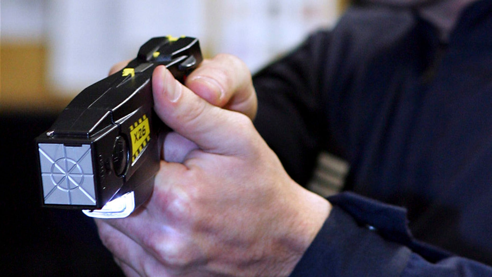 An unidentified  French Police officer presents a stun gun which is to be used experimentally by the anti-criminal brigades, in Paris, Tuesday Sept. 20, 2005. (AP Photo/Remy de la Mauviniere)