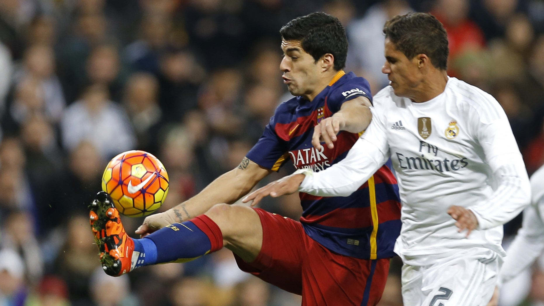Barcelona's Luis Suarez fights for the ball with Real Madrid's Raphael Varane during the first clasico of the season between Real Madrid and Barcelona at the Santiago Bernabeu stadium in Madrid, Spain, Saturday, Nov. 21, 2015.  (AP Photo/Francisco Seco)