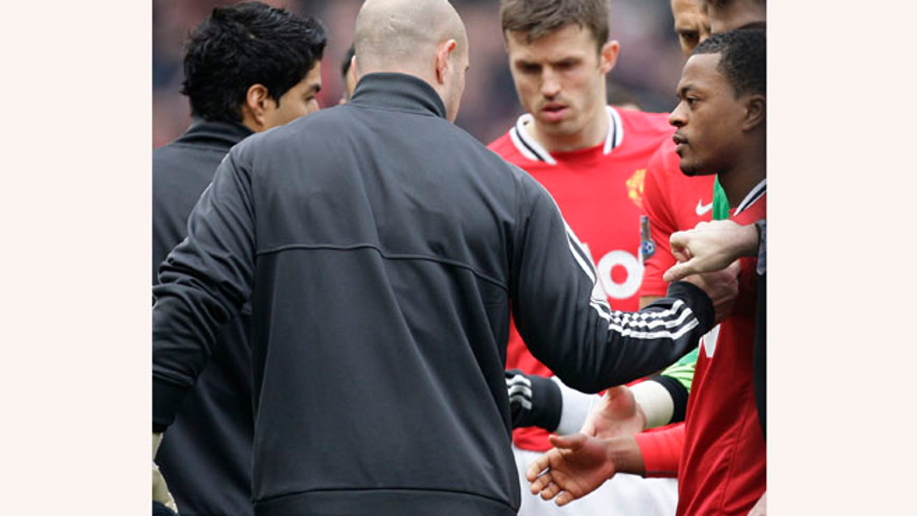 Manchester United's Patrice Evra, right, attempts to shake hands with Liverpool's Luis Suarez, left, during their English Premier League soccer match at Old Trafford Stadium, Manchester, England, Saturday, Feb. 11, 2012.  Suarez refused to shake the hand of the Manchester United defender Evra, their first meeting since the Liverpool forward was banned for eight matches for racially abusing Evra in October 2011.(AP Photo/Jon Super)