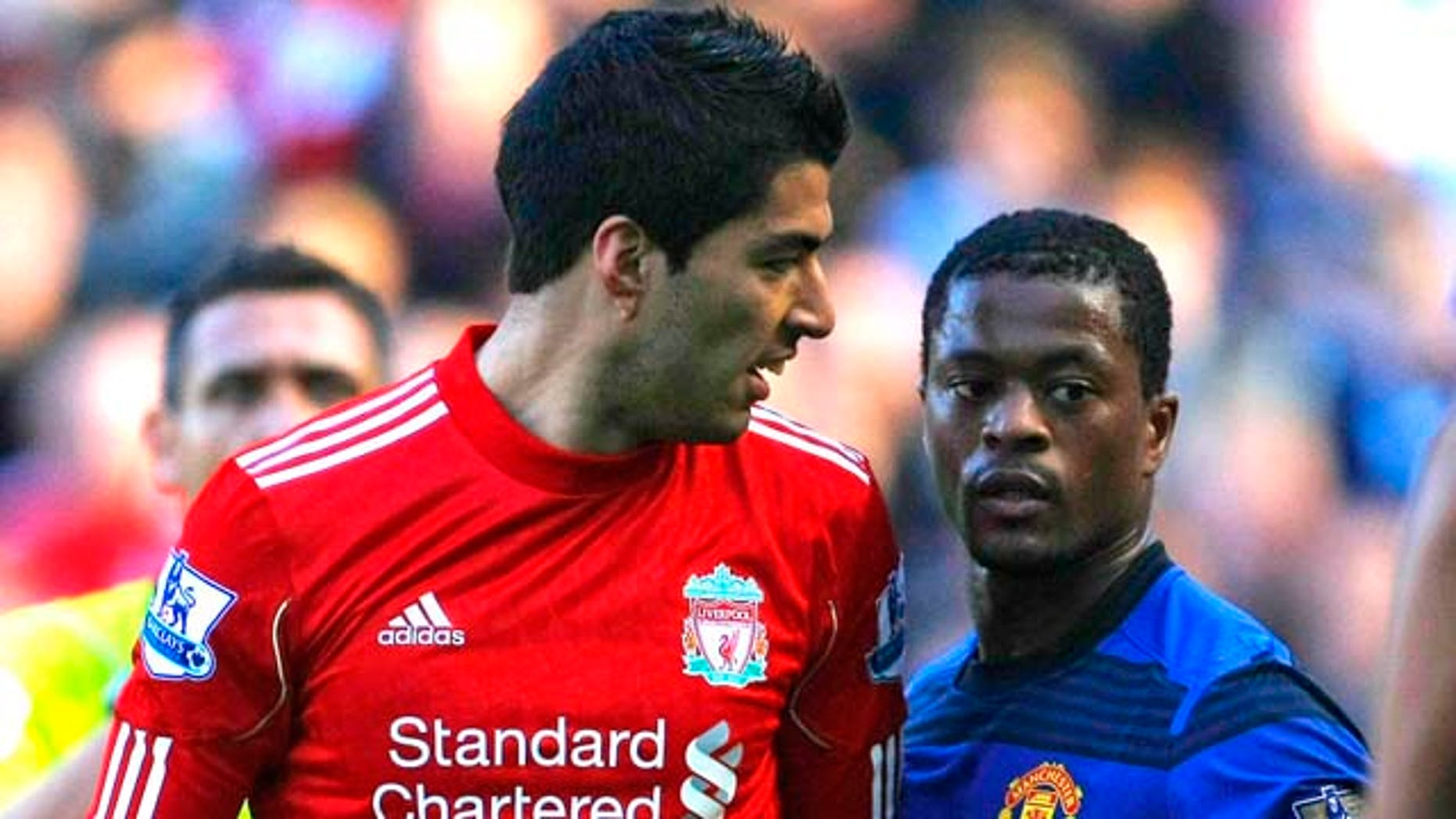In this photo taken Saturday, Oct. 15, 2011, Manchester United's Patrice Evra argues with Liverpool's Luis Suarez, left, during their English Premier League soccer match at Anfield, Liverpool, England. The English Football Association has launched an investigation into allegations from Manchester United's Patrice Evra that he was racially abused by Liverpool striker Luis Suarez during Saturday's Premier League match. (AP Photo/Tim Hales)