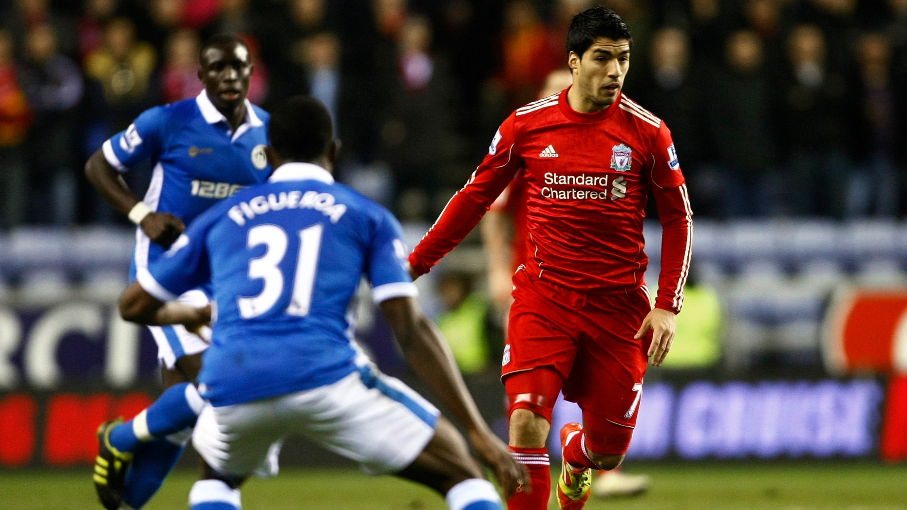 Liverpool's Luis Suarez, right, vies for the ball against Wigan's Maynor Figueroa, center, during their English Premier League soccer match at DW Stadium, Wigan, England, Wednesday Dec. 21, 2011. (AP Photo/Tim Hales)