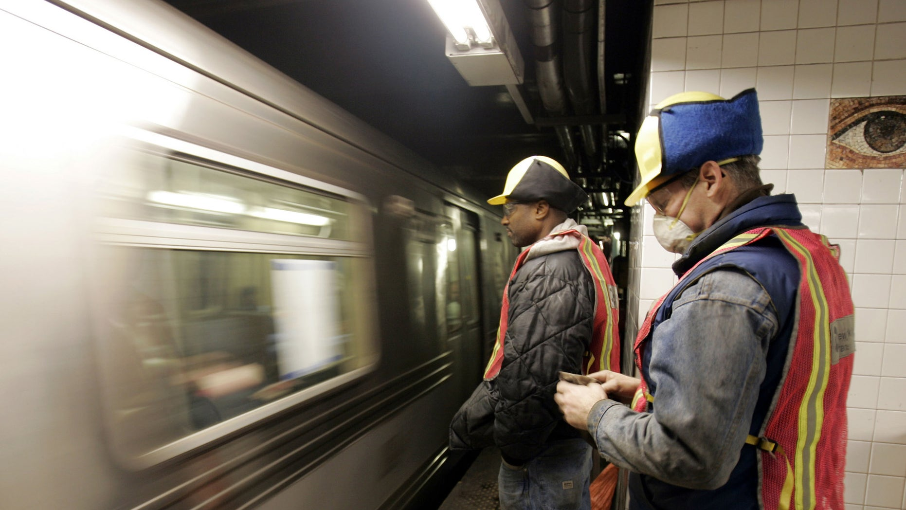New York City Transit workers watch as an A subway train enters the Chambers Street station,  Tuesday Jan. 25, 2005, near the scene of a fire apparently set by a homeless person Sunday, that spread to a vital equipment room.  Hundreds of thousands of riders on two of the city's busiest subway lines face significant delays and overcrowding lasting up to five years. (AP Photo/Richard Drew)