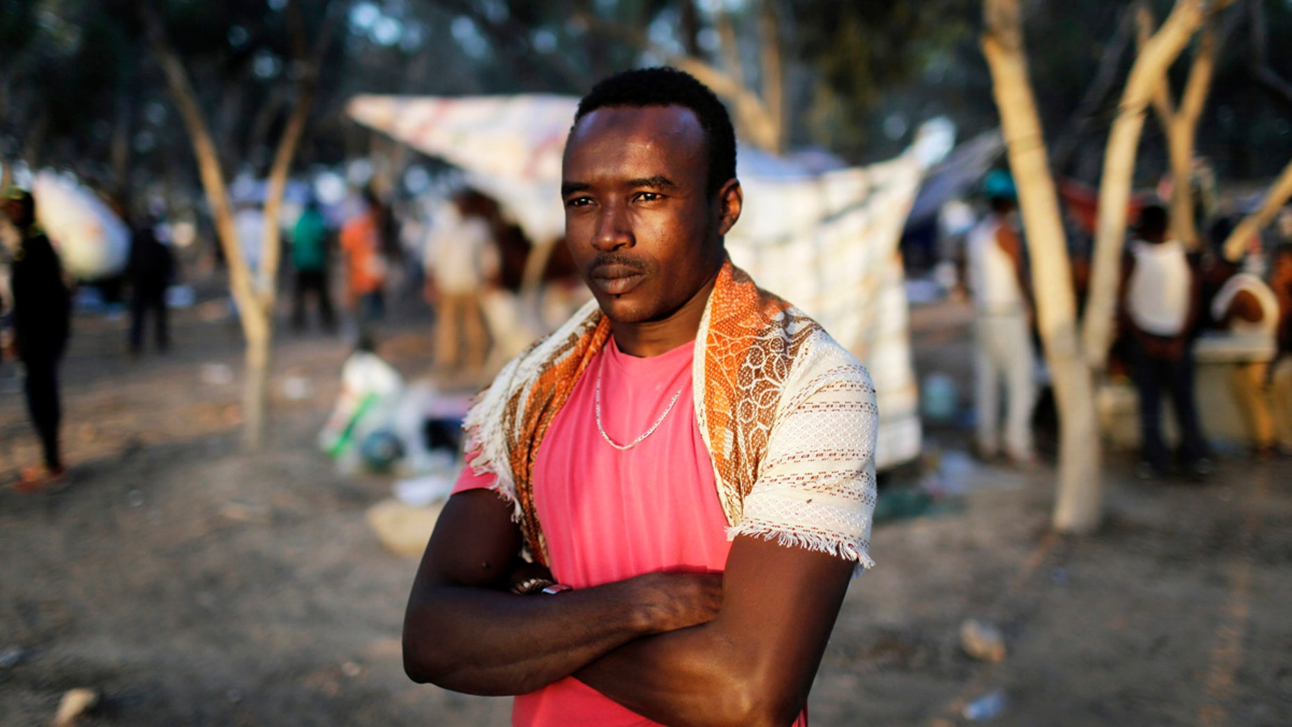 An African asylum seeker stands in the shade of trees during a protest after leaving Holot open detention centre in southern Israel's Negev desert.