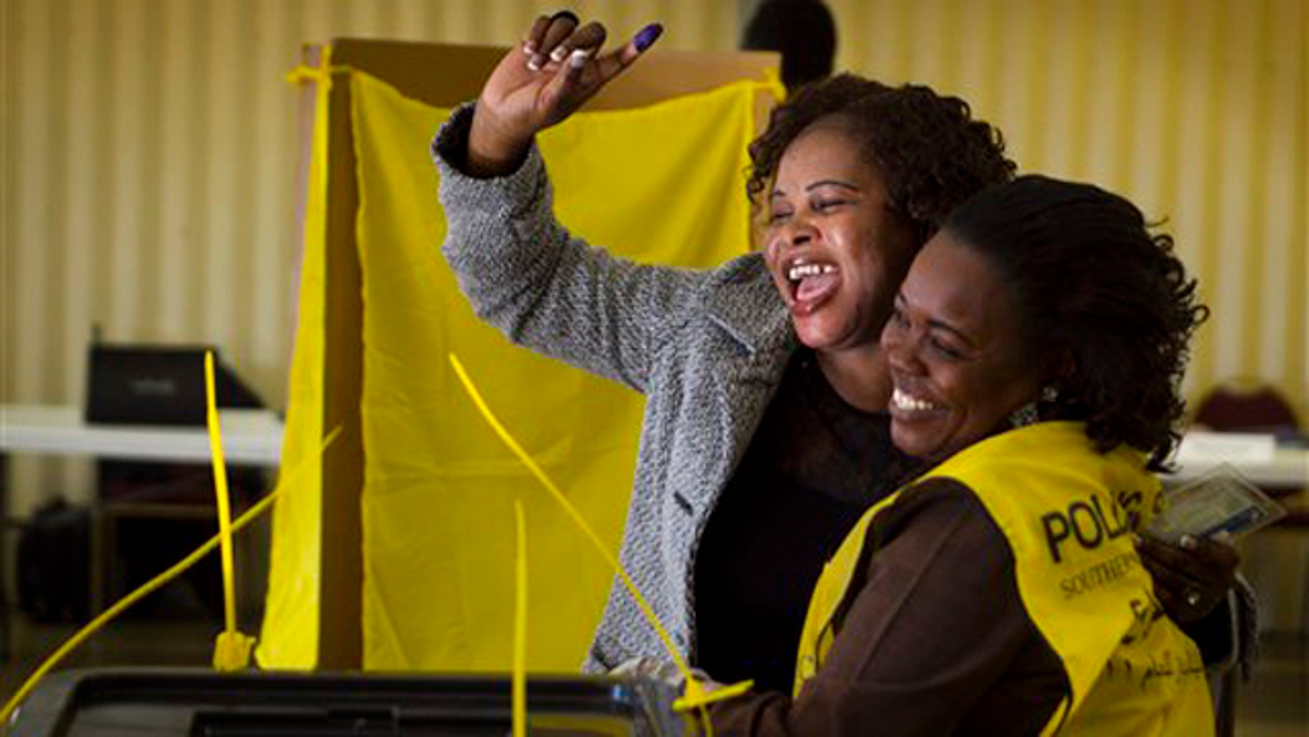 Jan 9, 2011: Helen Dembite, center, who came all the way from Queensland, Australia, just to vote cheers with her ink stained finger in the air next to Polling Staffer, Gisma Dabura, right, during the referendum vote on whether South Sudan will become independent from Sudan at St. James Catholic Church in Glendale, Ariz. The polling place in Glendale was one of only eight in the entire country. The ink stained finger shows that an individual voted and ensures the individual cannot vote again.