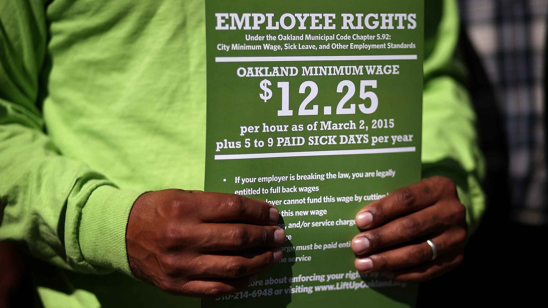 OAKLAND, CA - FEBRUARY 27:  A supporter of Oakland's minimum wage increase holds a sign during a celebration rally outside of Oakland City Hall on February 27, 2015 in Oakland, California. Dozens of minimum wage workers gathered on the steps of Oakland City Hall to celebrate a $3 increase in the city's minimum wage to $12.25 an hour. Voters passed measure FF in November with 81 percent voting in favor of the wage increase. The new wage goes into effect on March 2.  (Photo by Justin Sullivan/Getty Images)