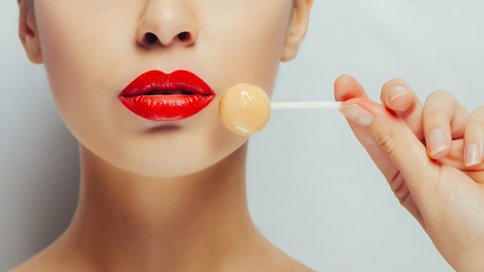 Young beautiful girl with lollipop in her mouth