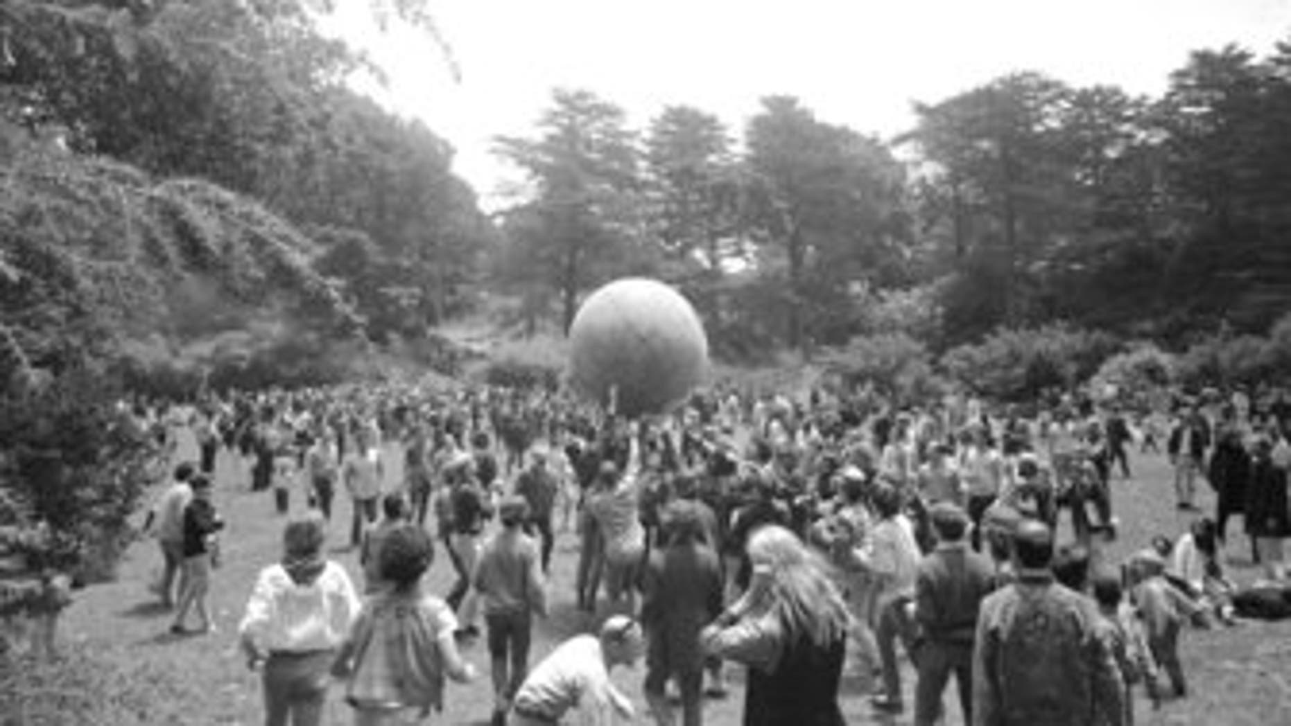 """People celebrating the summer solstice on June 21, 1967, carry a large ball, painted to represent a world globe, in the air during a gathering at Golden Gate Park in San Francisco on Day One of """"Summer of Love."""" (AP Photo/File)"""
